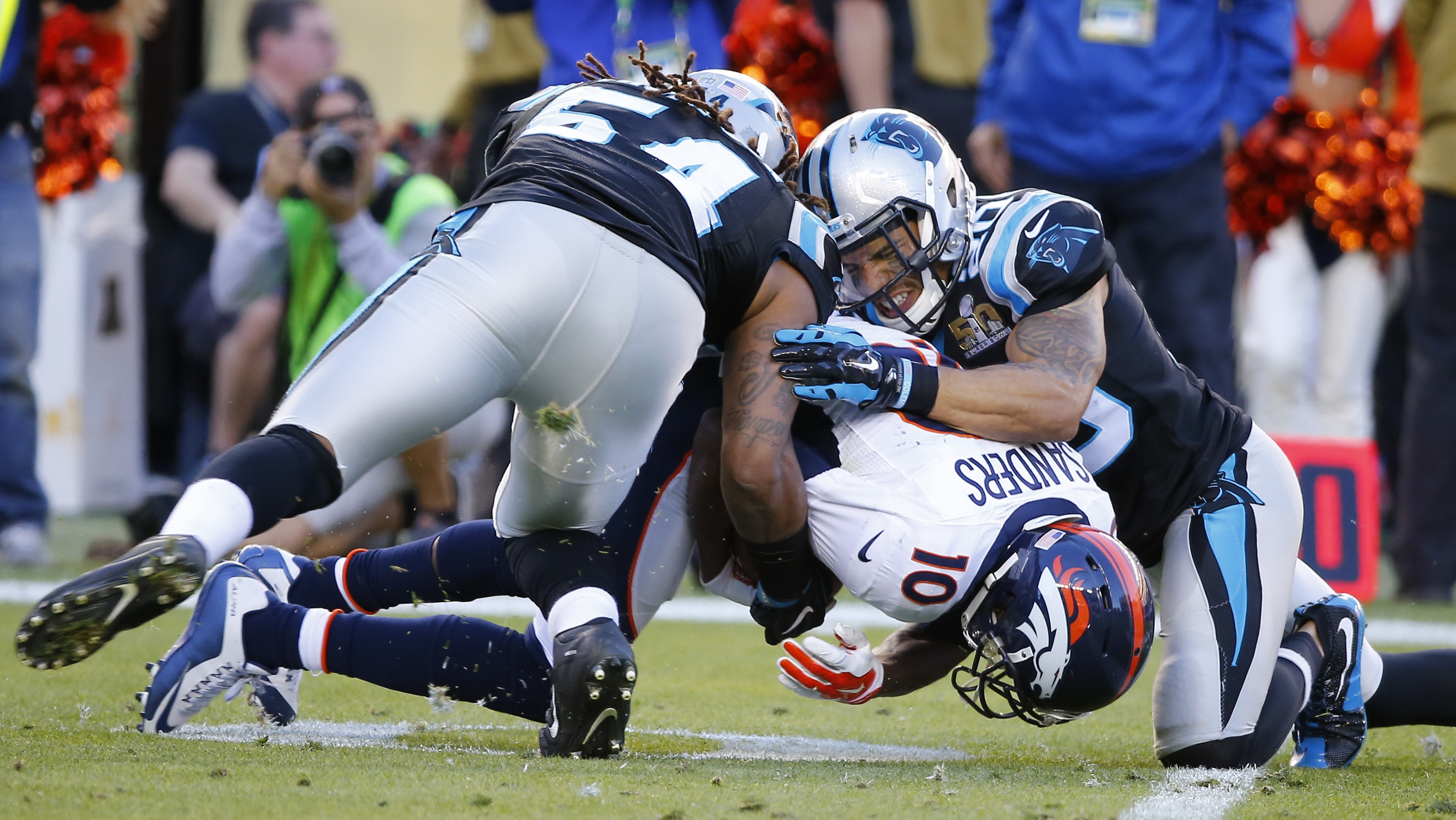 Denver Broncos' Sanders is tackled after a reception by Carolina Panthers' Thompson and Finnegan during the first quarter of the NFL's Super Bowl 50 football game in Santa Clara