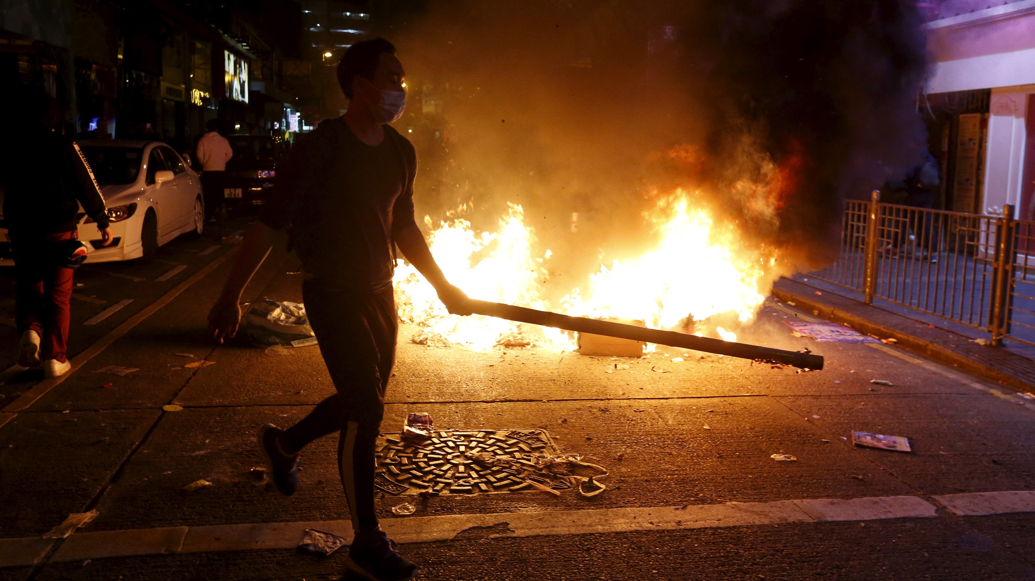 A protester carrying a rod walks past a fire at a junction in Mongkok in Hong Kong, China February 9, 2016. Riot police used batons and pepper spray early on Tuesday to quell fights after authorities tried to move illegal street vendors from a working-class Hong Kong district, the worst street clashes since pro-democracy protests in late 2014.