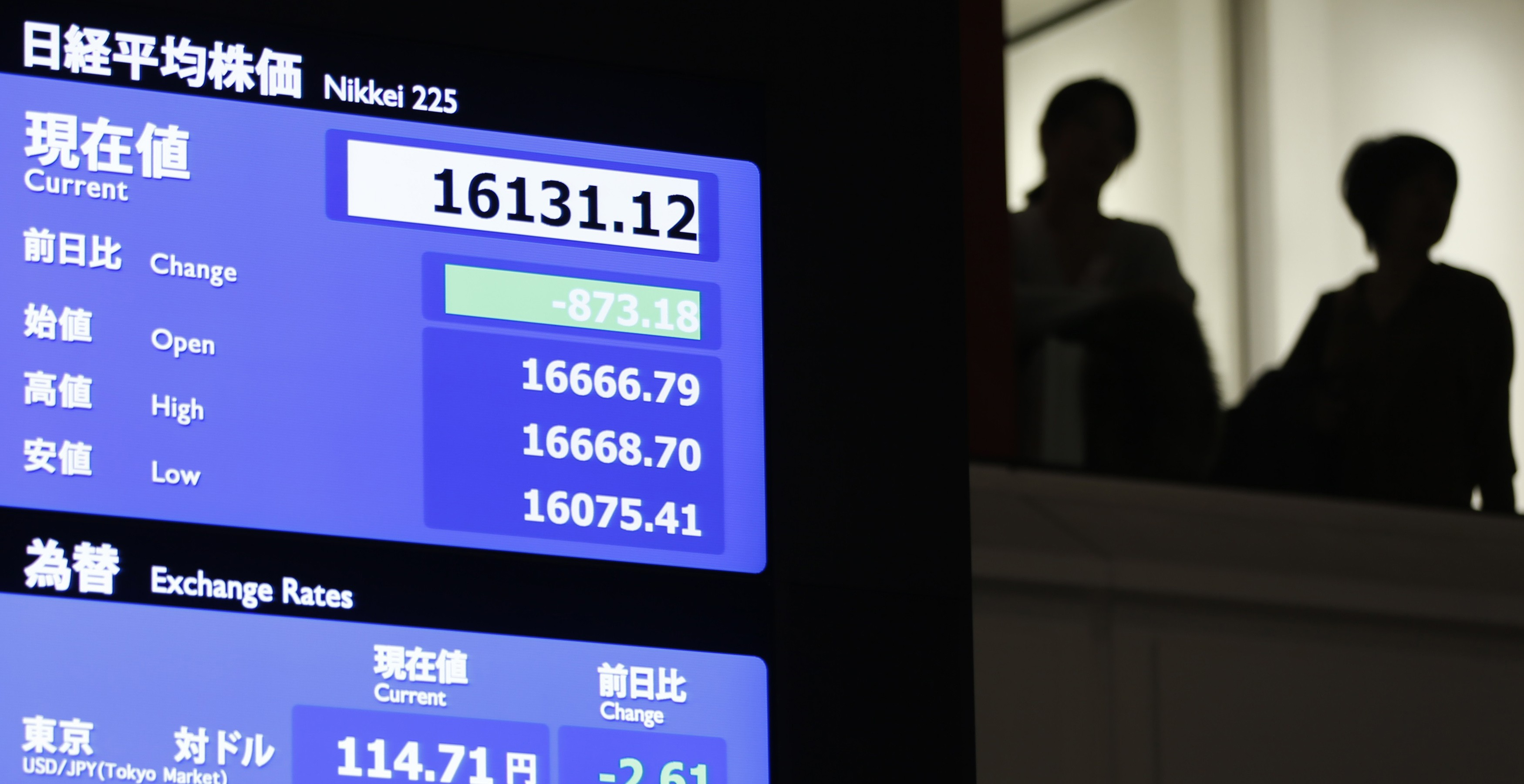 Visitors stand next to an electronic board showing the Japan's Nikkei average and the Japanese yen's exchange rate against the U.S. dollar at the Tokyo Stock Exchange in Tokyo
