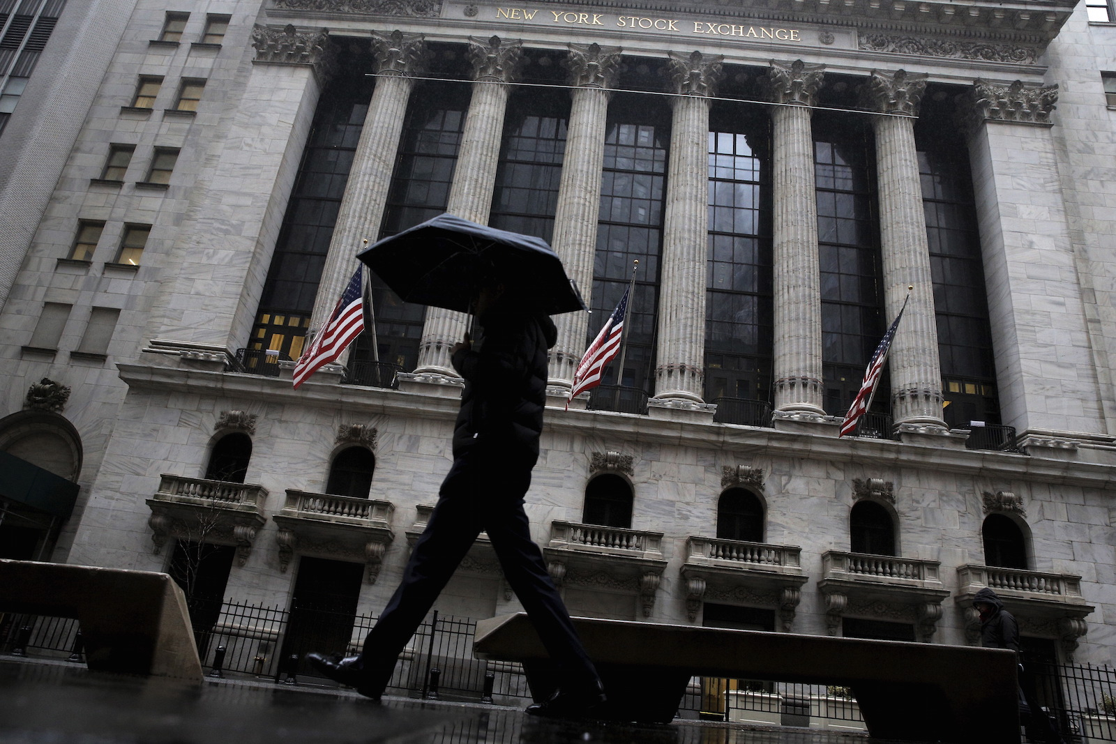 A man passes by the New York Stock Exchange during a rain storm in New York February 24, 2016.