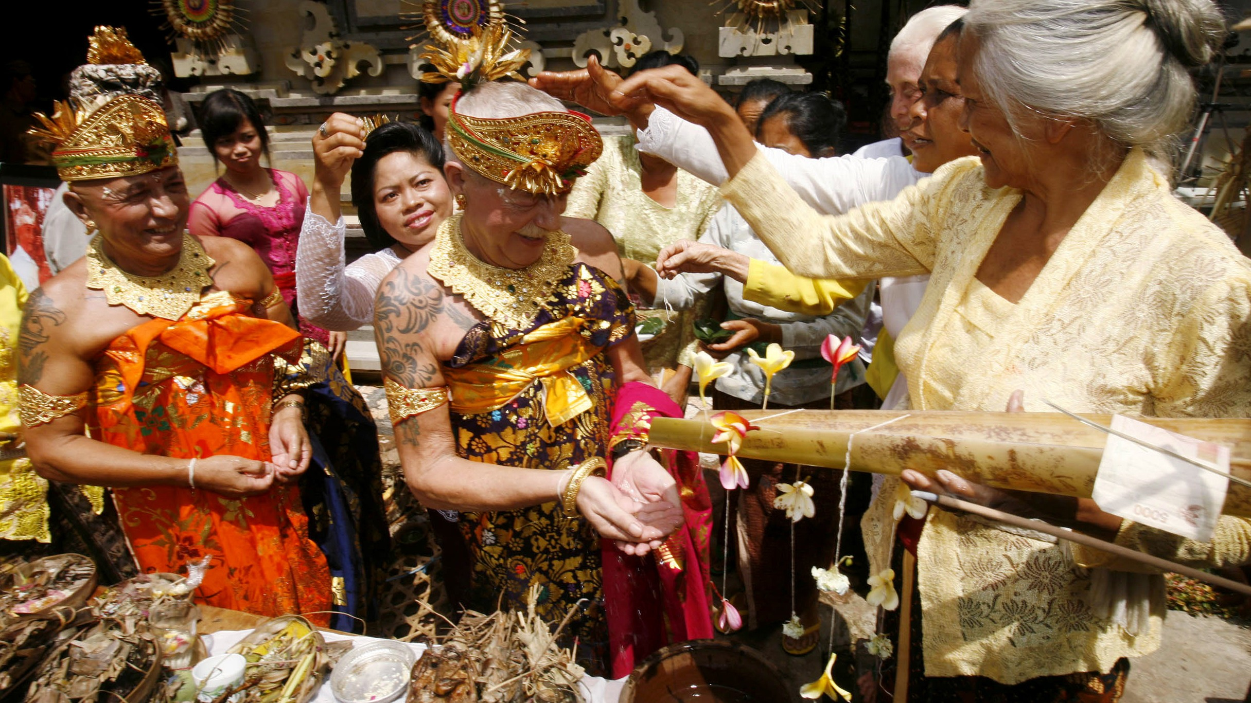 Holy water is sprinkled on Dutch gay couple Hendricus Johannes Deijkers and Christianus Huijbregts during their religion conversion ceremony in Bali