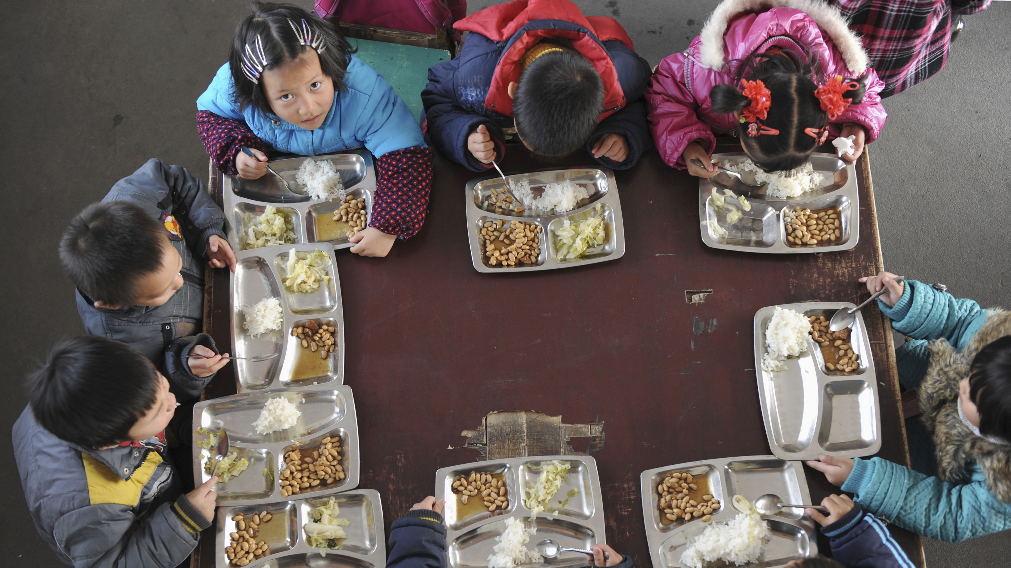 """Children have lunch in their classroom at a kindergarten in Jiaxing, Zhejiang province December 21, 2010. Preschools are the """"weakest"""" part of China's education system, according to the Chinese government which says it will generally improve the country's kindergartens to ensure a quality start for children, Xinhua News Agency reported. REUTERS/Stringer (CHINA - Tags: EDUCATION POLITICS) CHINA OUT. NO COMMERCIAL OR EDITORIAL SALES IN CHINA - RTXVXC5"""