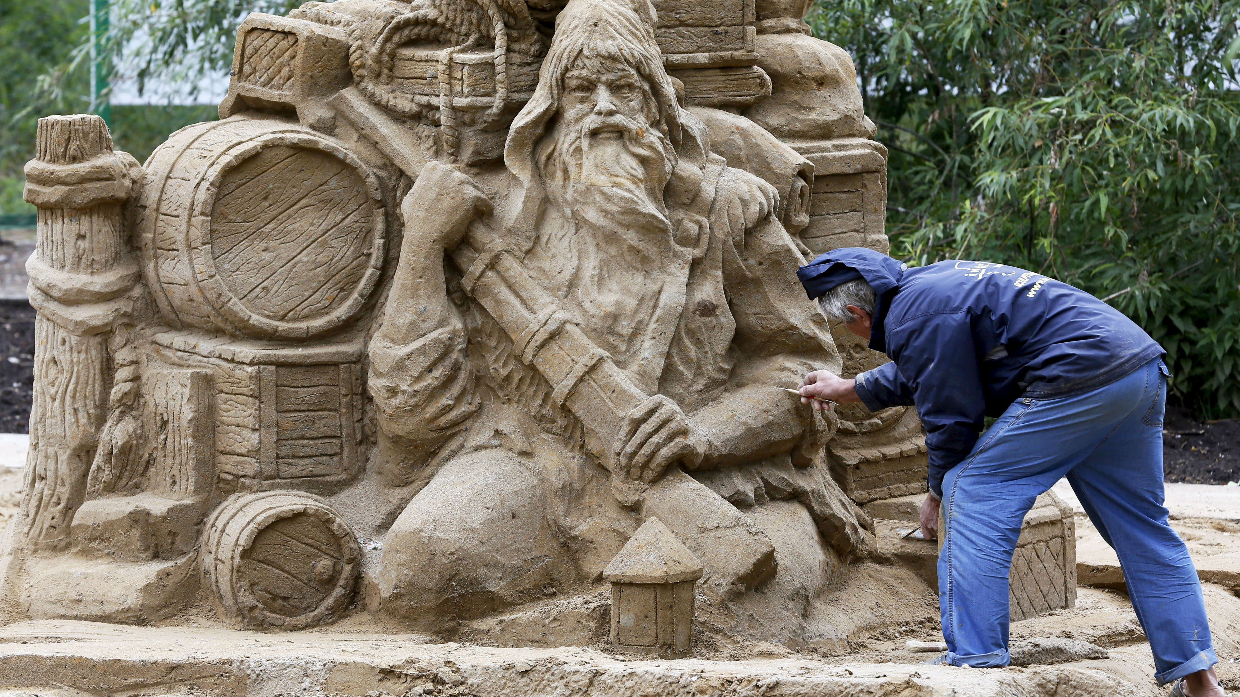 """Russian sculptor Valery Zaitsev works on the """"Robinson Crusoe"""" sand sculpture during the preparations for the """"Favorite Book"""" thematic exhibition of sand sculptures in the Siberian city of Krasnoyarsk, Russia, June 25, 2015. The exhibition, created by professional artists from several Siberian cities and students of the Krasnoyarsk State Arts Institute, will be opened on June 27, according to organizers. Reuters/Ilya Naymushin"""