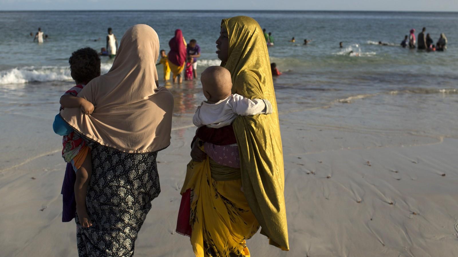 Women carry children as they chat on Lido beach in Mogadishu November 13, 2013. REUTERS/Siegfried Modola (SOMALIA - Tags: SOCIETY TRAVEL) - RTX15C07