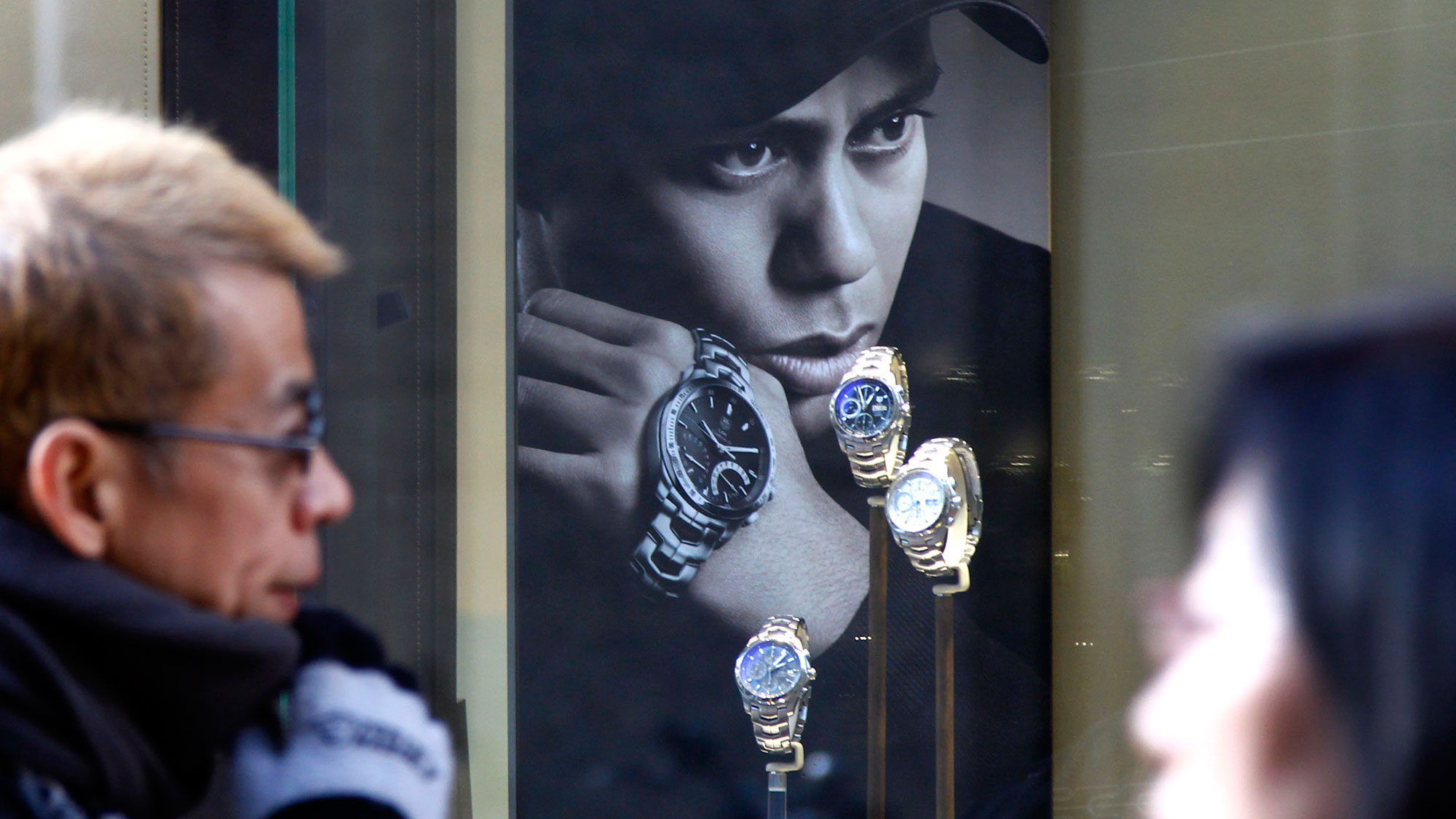 "FILE - This Dec. 15, 2009 file photo shows people walking by a Swiss watch shop displaying watches along with U.S. golfer Tiger Woods' portrait in Tokyo. Swiss watchmaker Tag Heuer says it's ended its 10-year commercial relationship with Tiger Woods and hopes he can ""overcome his difficulties."" (AP Photo/Koji Sasahara, File)"