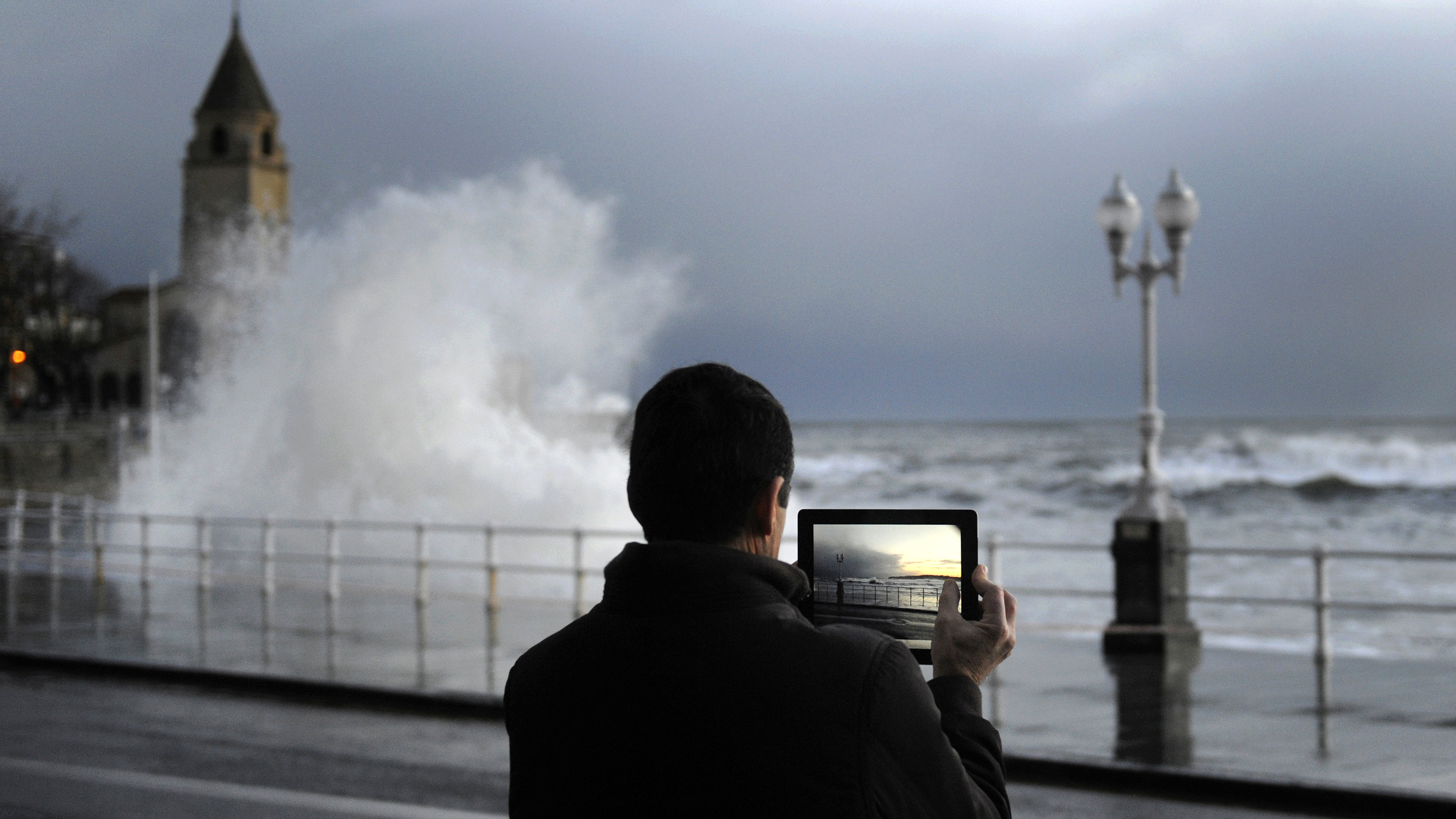A man takes pictures as huge waves crash onto San Lorenzo's beach in Gijon, in the northern Spanish region of Asturias February 5, 2014. REUTERS/Eloy Alonso (SPAIN - Tags: ENVIRONMENT)