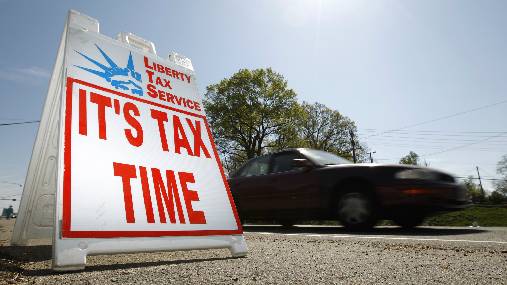 A car passes a sign advertising tax return services in Falls Church, Virginia April 8, 2010. The deadline for Americans to file their 2009 income tax returns in April 15th.