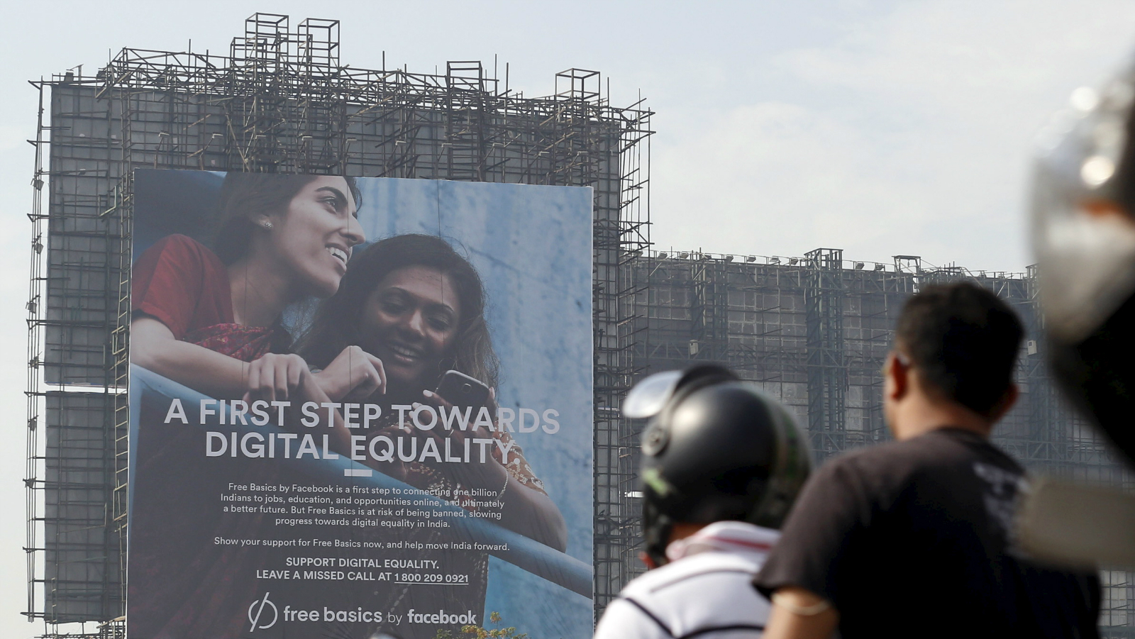 Motorists ride past a billboard displaying Facebook's Free Basics initiative in Mumbai, India, December 30, 2015. India has become a battleground over the right to unrestricted Internet access, with local tech start-ups joining the front line against Facebook Inc founder Mark Zuckerberg and his plan to roll out free Internet to the country's masses. The Indian government has ordered Facebook's Free Basics plan on hold while it decides what to do. Picture taken December 30, 2015.