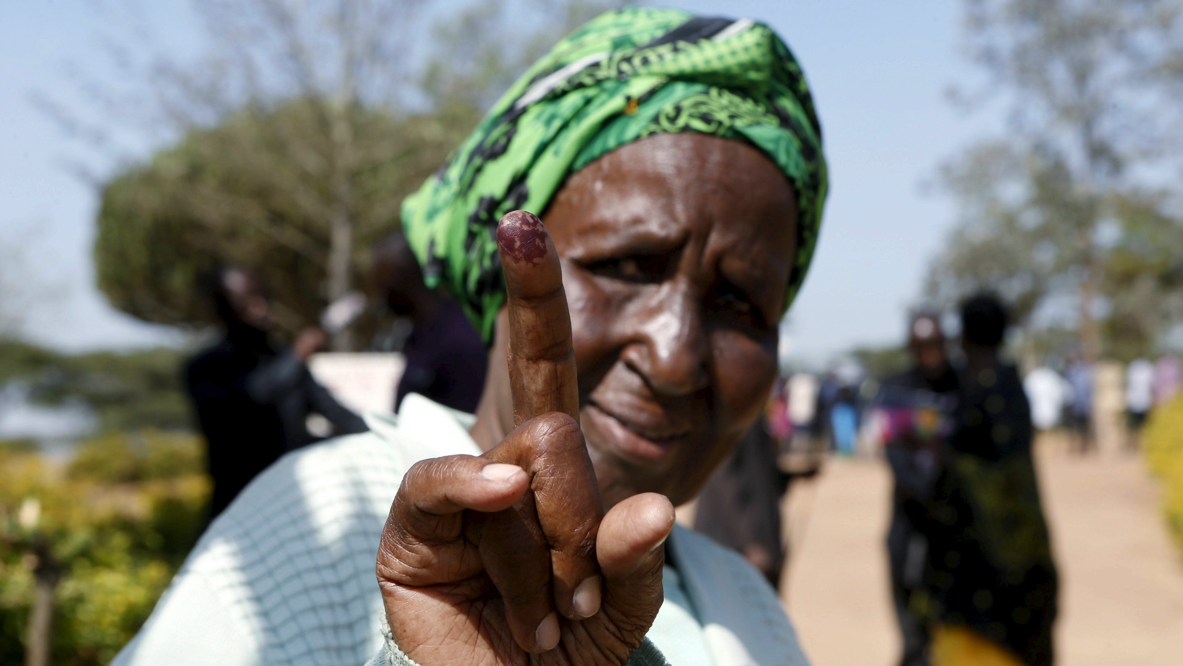 An elderly woman displays her inked finger after casting her vote during the presidential elections in Kirihura in western Uganda, February 18, 2016. Ugandans start casting votes on Thursday to decide whether to give Yoweri Museveni, in power for three decades, another term in office.