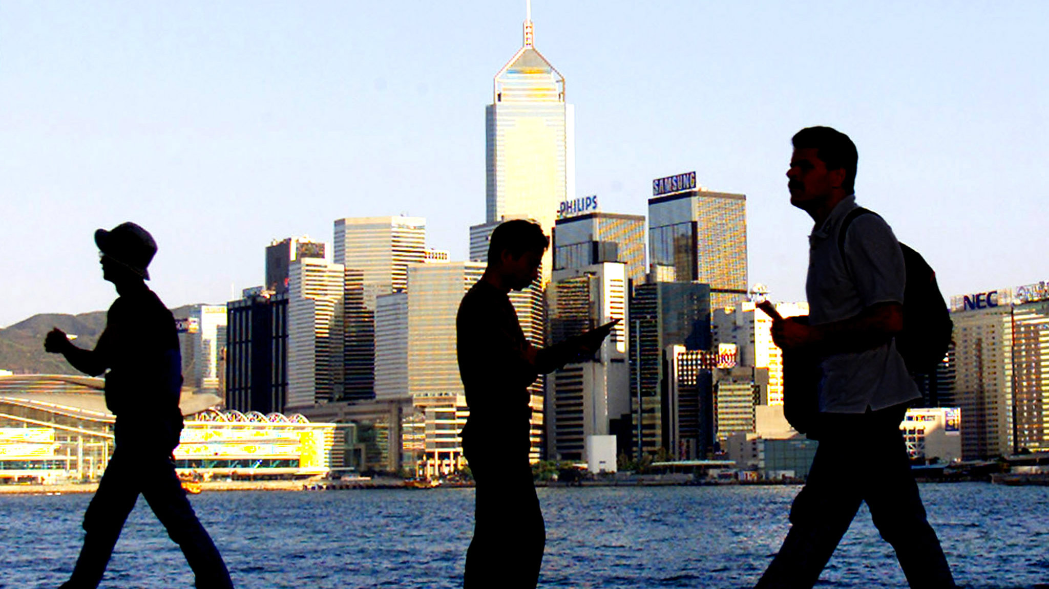 Passersby walk along the waterfront of Hong Kong's commercial Central district February 22, 2002. Hong Kong said it was facing serious budget problems which threatened to wipe out the enormous fiscal reserves, used to back its currency peg to the U.S. dollar, the pillar of financial stability in the territory's extremely open economy, in just seven years. REUTERS/Bobby Yip  BY/JD