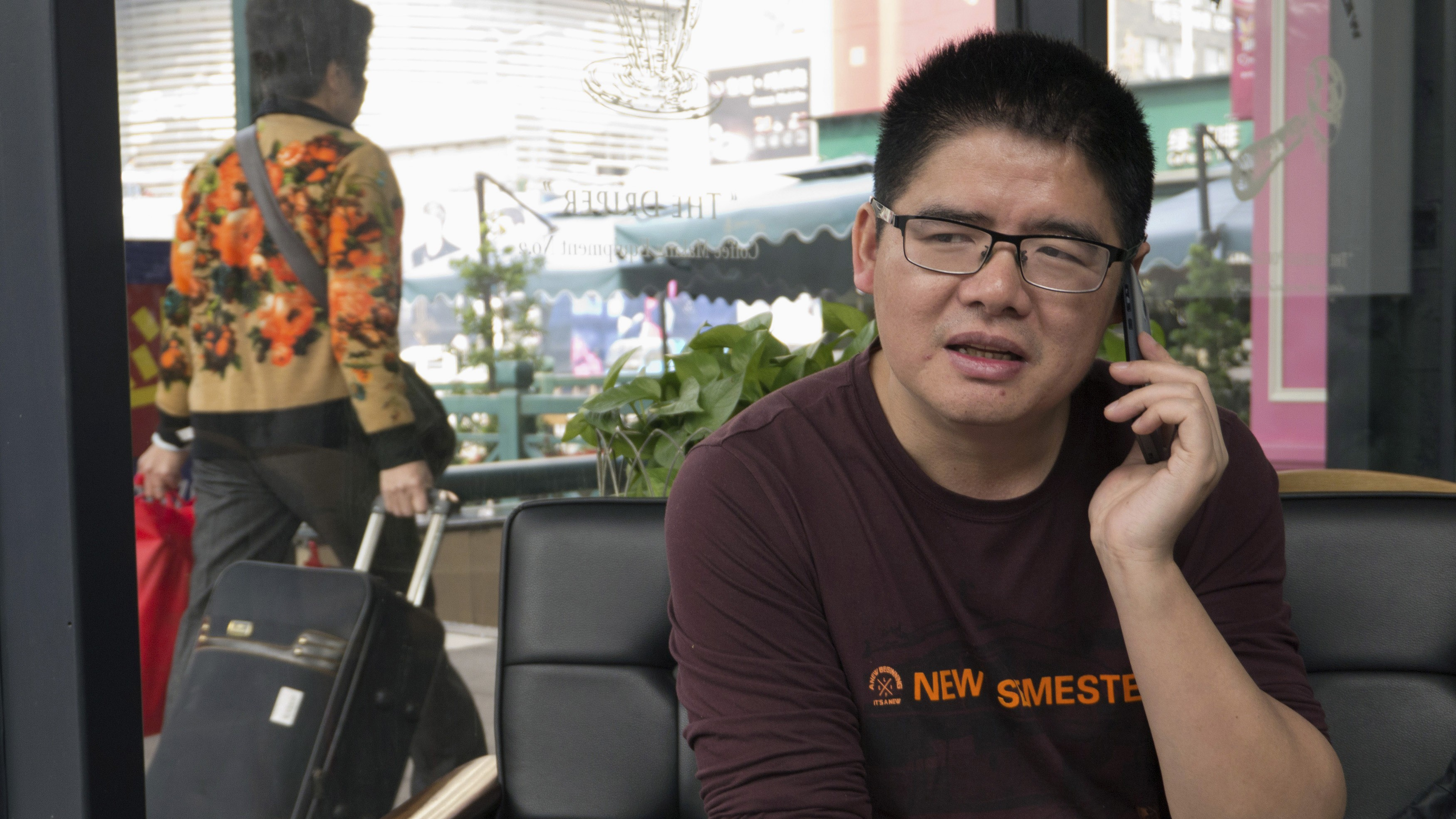 Zeng Feiyang, director of the Guangdong Panyu Migrant Workers Center, talks on his phone during an interview in Guangzhou