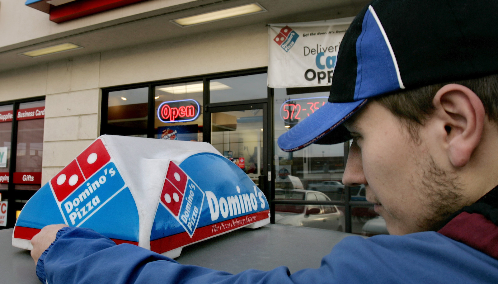 Domino's Pizza delivery person Brandon Christensen plugs in the company sign atop his car as the sun sets, Wednesday, Feb. 21, 2007, in Sandy, Utah.  Domino's Pizza Inc. said Frida, Feb. 23, 2007 fourth-quarter profit fell 23 percent from year-ago results that included a gain on the sale of an investment in a franchise operation in Mexico.