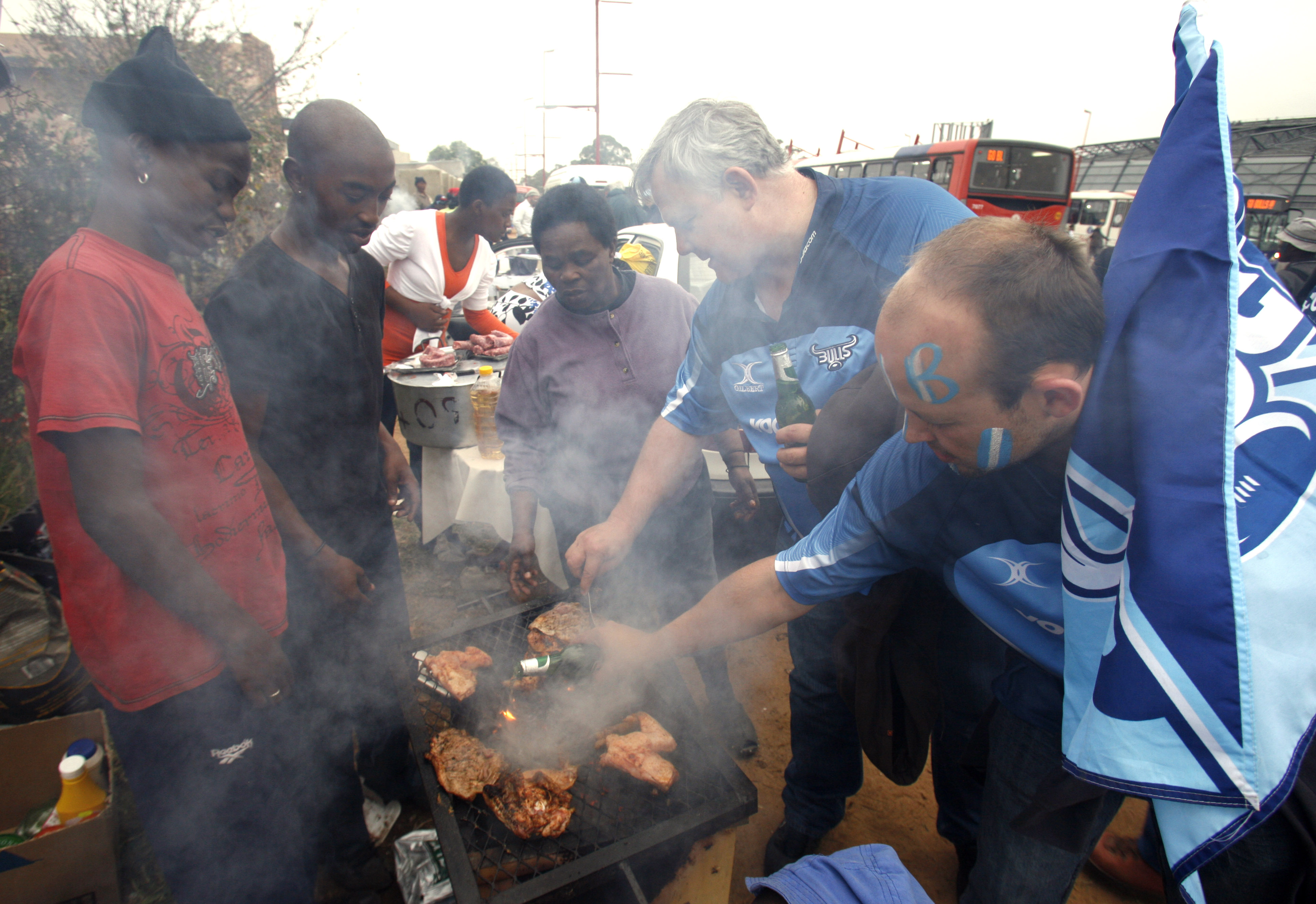 Bulls supporter pour some beer onto their braai meat at a local shebeen or bar, before a kick-off for the finals of the Super 14 rugby match against Stormers at the Orlando stadium in Soweto, South Africa, Saturday May 29, 2010. (AP Photo/Themba Hadebe)