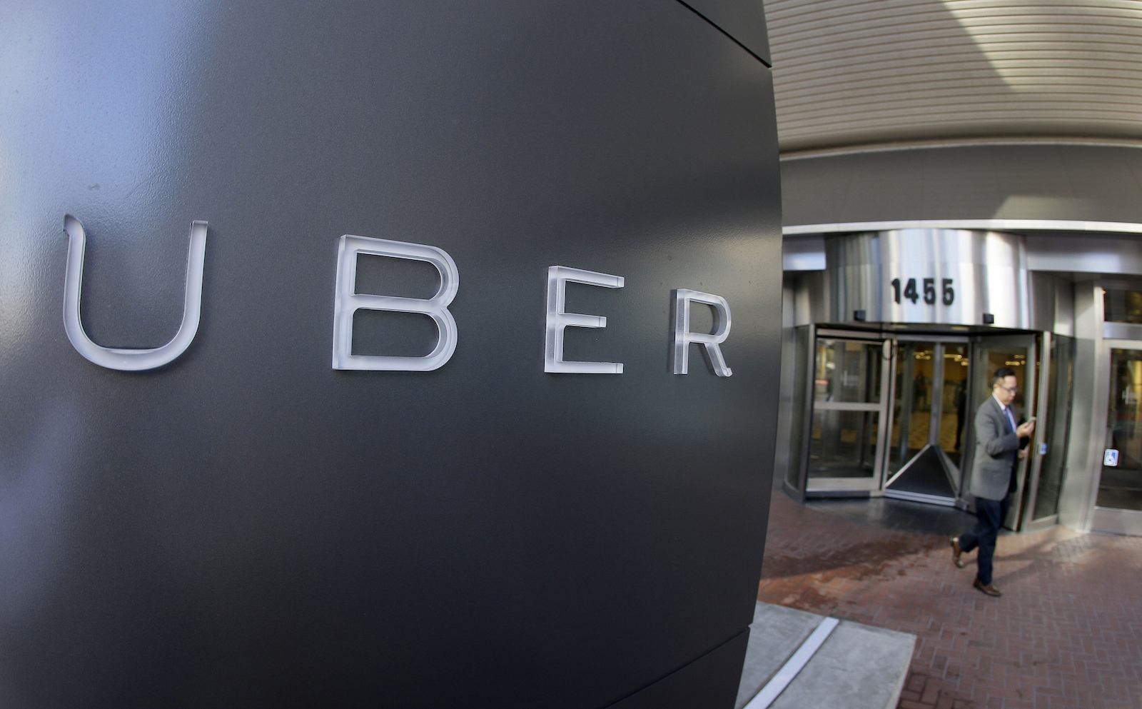 FILE - In this Dec. 16, 2015, file photo, a man leaves the headquarters of Uber in San Francisco. The killings in Kalamazoo, Michigan, raised anew a question that has dogged Uber and other taxi competitors. Their rides may be cheaper and more conveniently hailed than a cab, but the question is are they as safe.