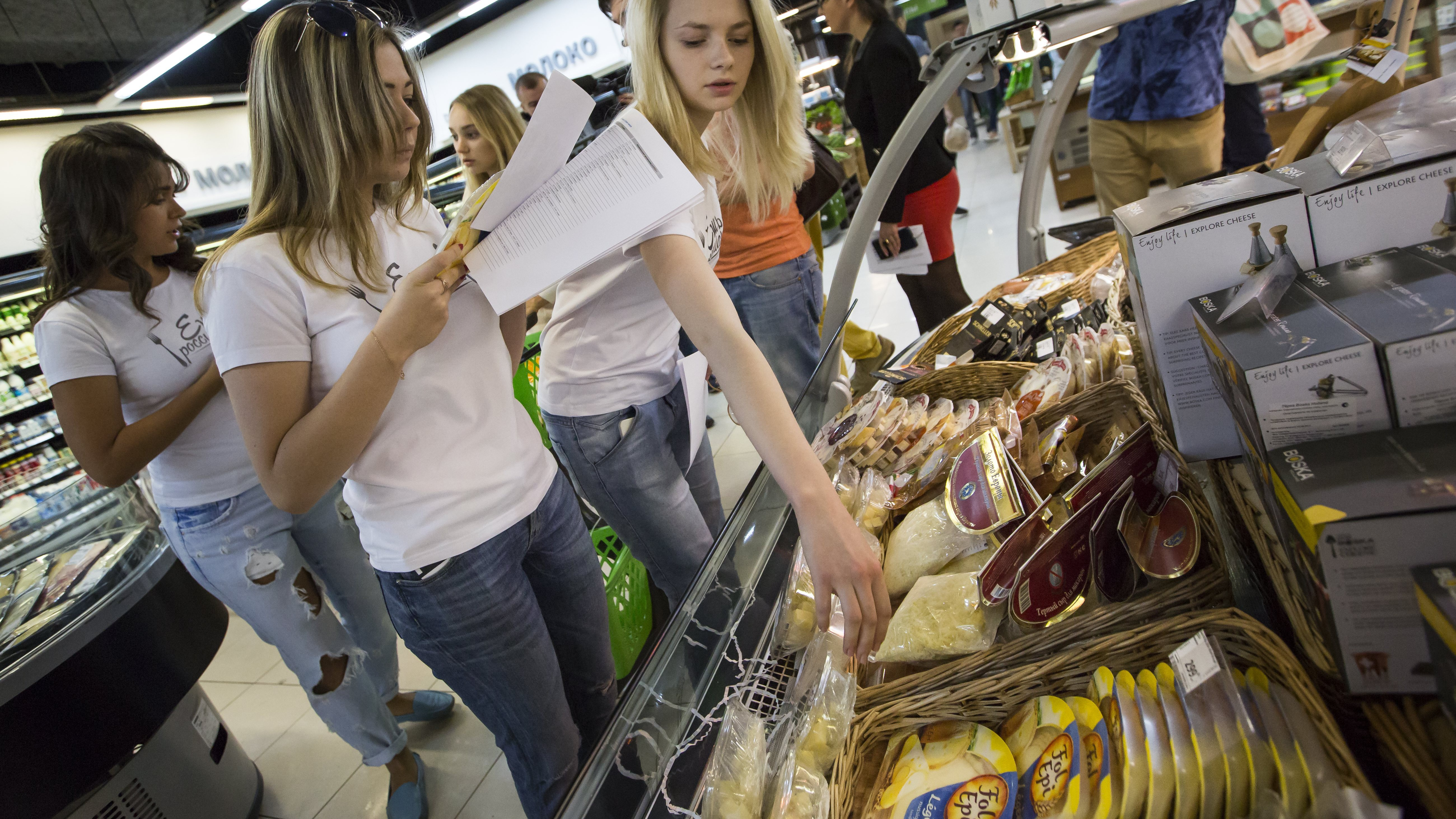 """In this photo taken on Tuesday, Aug.  4, 2015, a group of activists, members of """"Eat the Russian food"""" movement, check food at a Moscow food store in Moscow, Russia. Russia has marked the one-year anniversary of its ban on Western agricultural products with an order to destroy contraband food, a move that has raised controversy amid the nation's economic downturn. Importers have found numerous loopholes to bypass the Kremlin's ban on Western food, and pro-Kremlin activists have sought to help the government to catch illegal imports. (AP Photo/Alexander Zemlianichenko)"""
