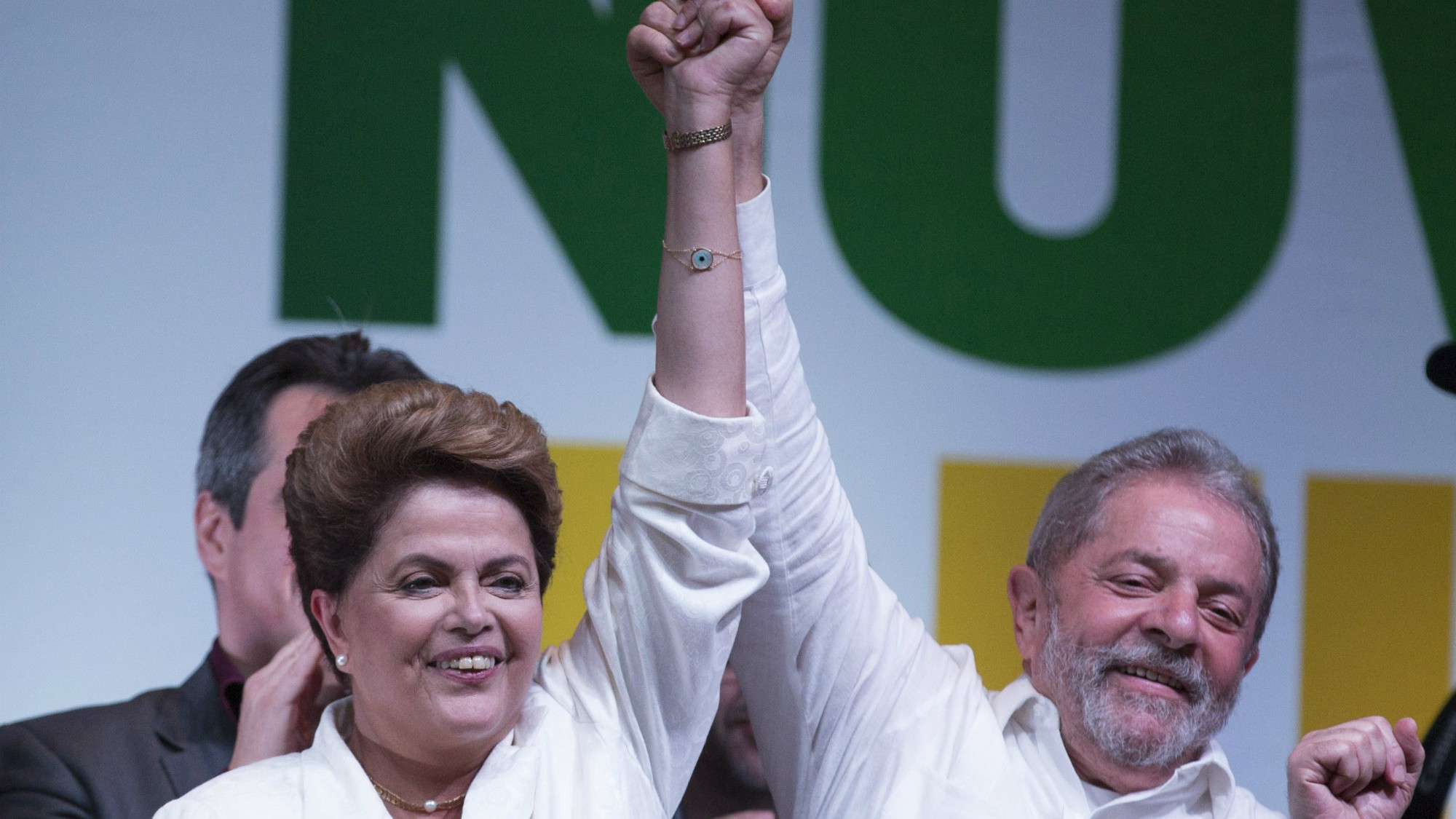 Brazil's President Dilma Rousseff celebrates with Brazil's Former President Luiz Inacio Lula da Silva at a press conference in a hotel in Brasilia, Brazil, Sunday, Oct. 26, 2014.