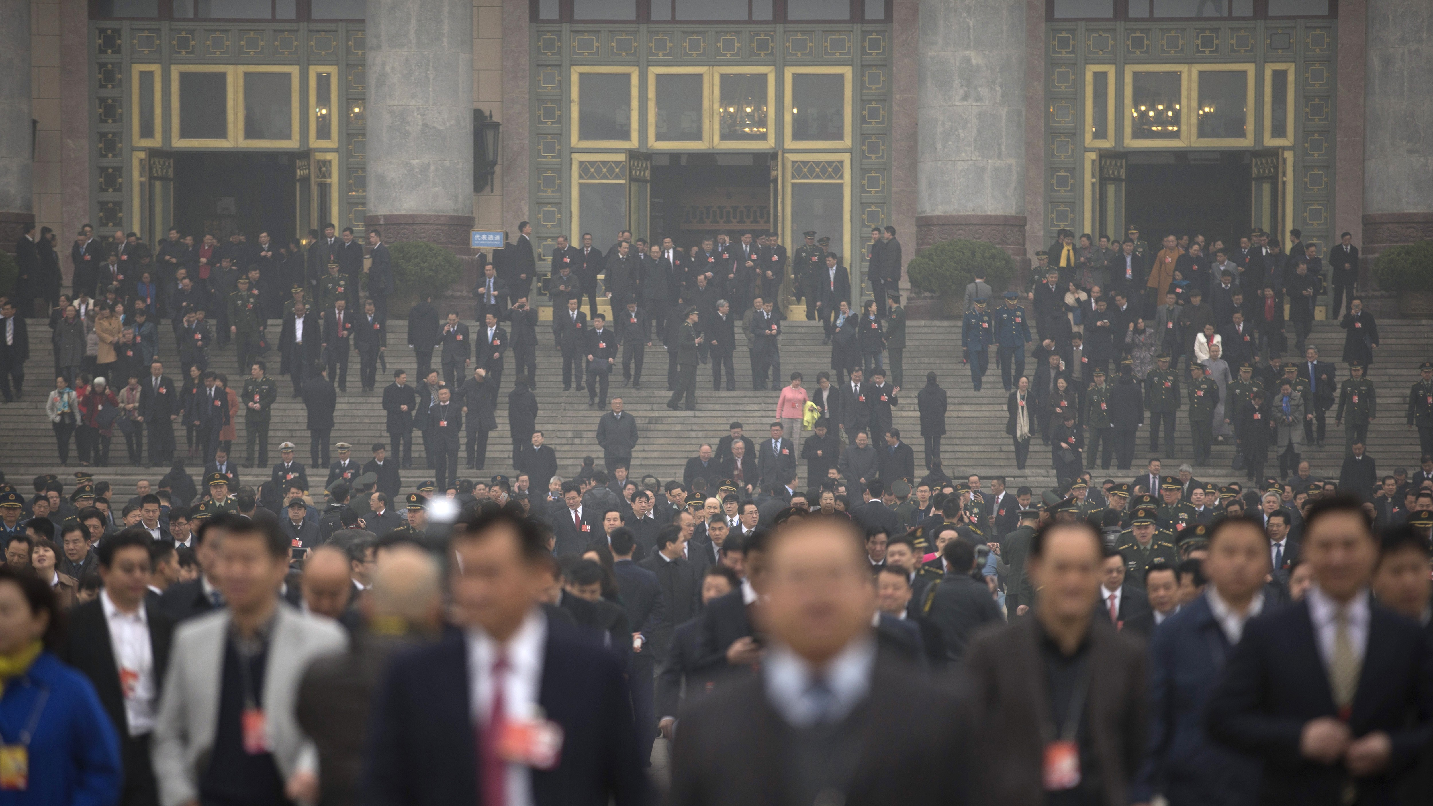 Delegates leave the Great Hall of the People in Beijing following a meeting ahead of Saturday's opening session of China's National People's Congress (NPC), Friday, March 4, 2016. The political conclave comes as China's leaders are being tested by new challenges including an economy that has slowed to a 25-year low, global uncertainty over the country's tumultuous stock markets and currency movements, and tensions over the South China Sea. (AP Photo/Mark Schiefelbein)