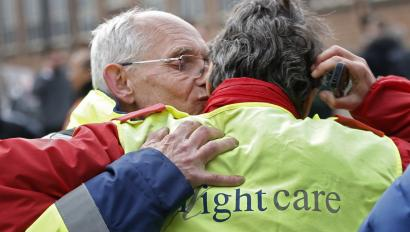 Airport workers embrace as they leave the scene of explosions at Zaventem airport near Brussels, Belgium, March 22, 2016.