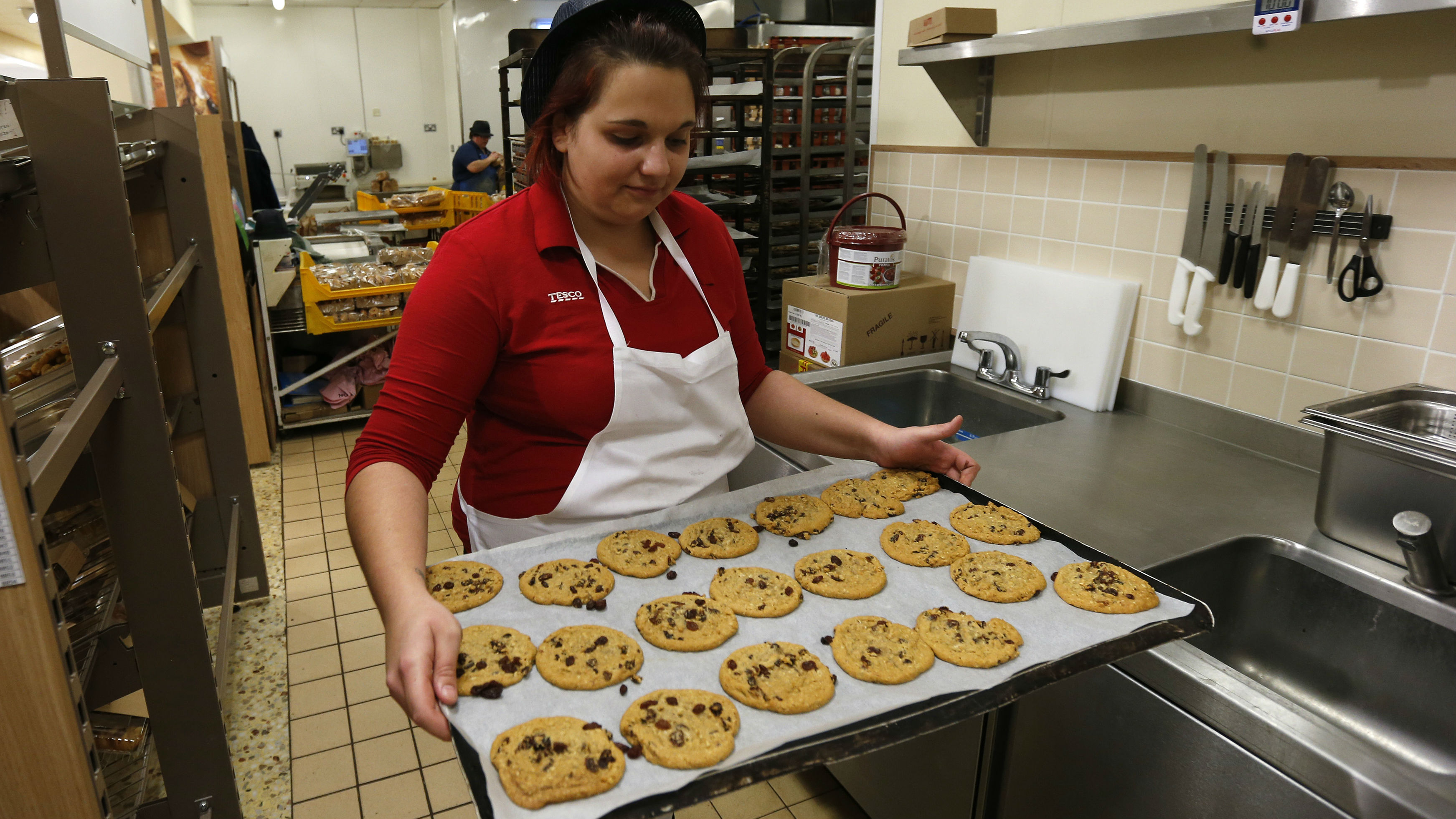 Tesco employee Jessica Francis carries a tray of chocolate chip cookies in the bakery at a Tesco shop in Bishop's Stortford, southern England November 26, 2012. Eight months ago Tesco Plc chief executive Phil Clarke set out a 1 billion pound ($1.6 billion) recovery plan to arrest the group's worrying loss of market share. How well it's working may start to emerge next week. Picture taken November 26, 2012.