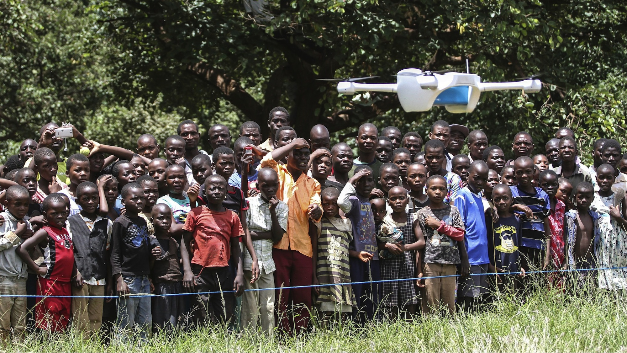 Children in Lilongwe, Malawi watch a drone designed to deliver HIV tests to hospitals