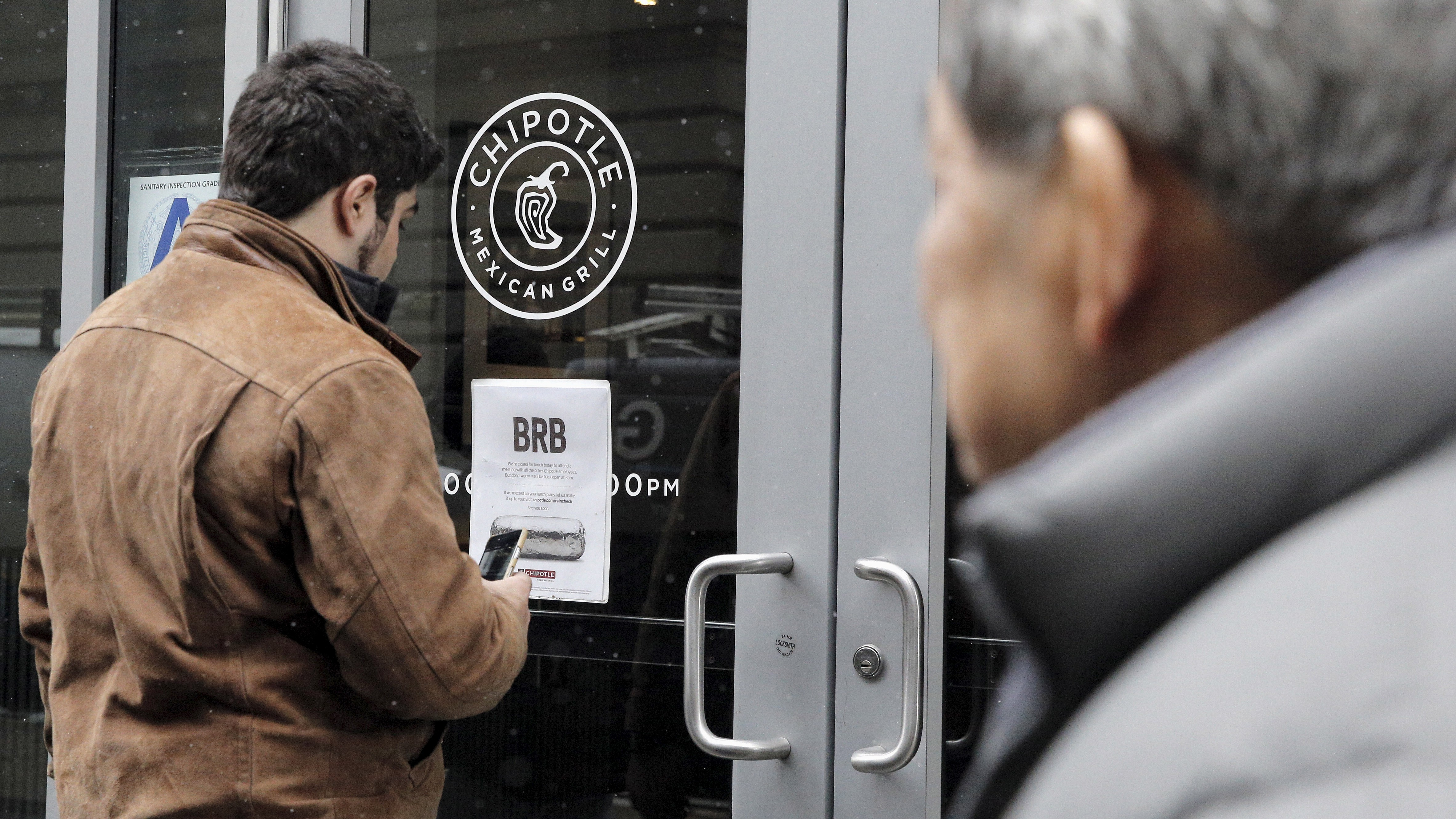 A customer reads a sign posted on the door of a Chipotle Mexican Grill in New York February 8, 2016.