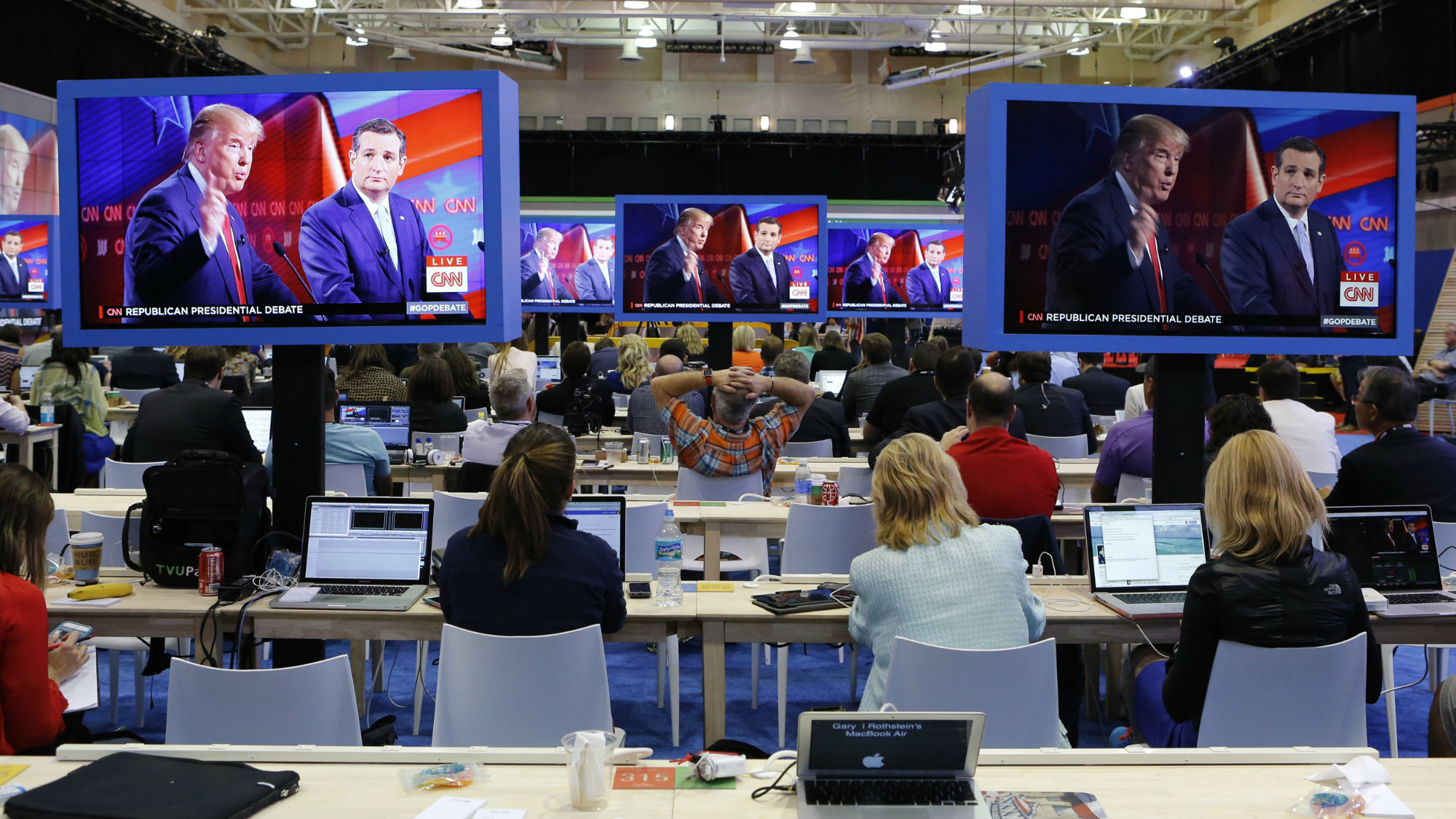 Journalists watch Republican U.S. presidential candidates Donald Trump (L) and Ted Cruz debate on large video monitors in the media filing center during the Republican U.S. presidential candidates debate sponsored by CNN at the University of Miami in Miami, Florida March 10, 2016.