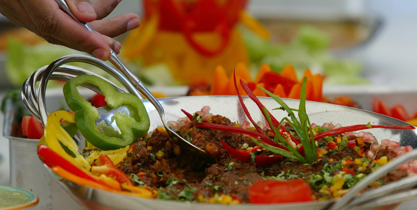 Winners of the best Bangladesh curry competition Tariq Mahmood, and Mohamed Rafiq, unseen, spoon out some of their food at a tasting in London Thursday Sept. 9, 2004. Mahmood and Rafiq who own a curry house in Bradford, in the north of England won the competition against seven other London based curry house's at a tasting in London's Brick Lane centre of the Bangladeshi community in Britain. The food is a boned lamb and lentil based curry.