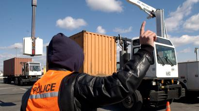 An officer from the United States Customs and Border Protection service inspect the contents of shipping containers with a truck mounted X-ray machine arriving at Port Newark from all around the world, in Newark, New Jersey February 24, 2006. Powerful Washington lawmakers citing security concerns are pushing emergency legislation to block a controversial deal that would place management of six major U.S. ports in the hands of a state-owned Arab company.