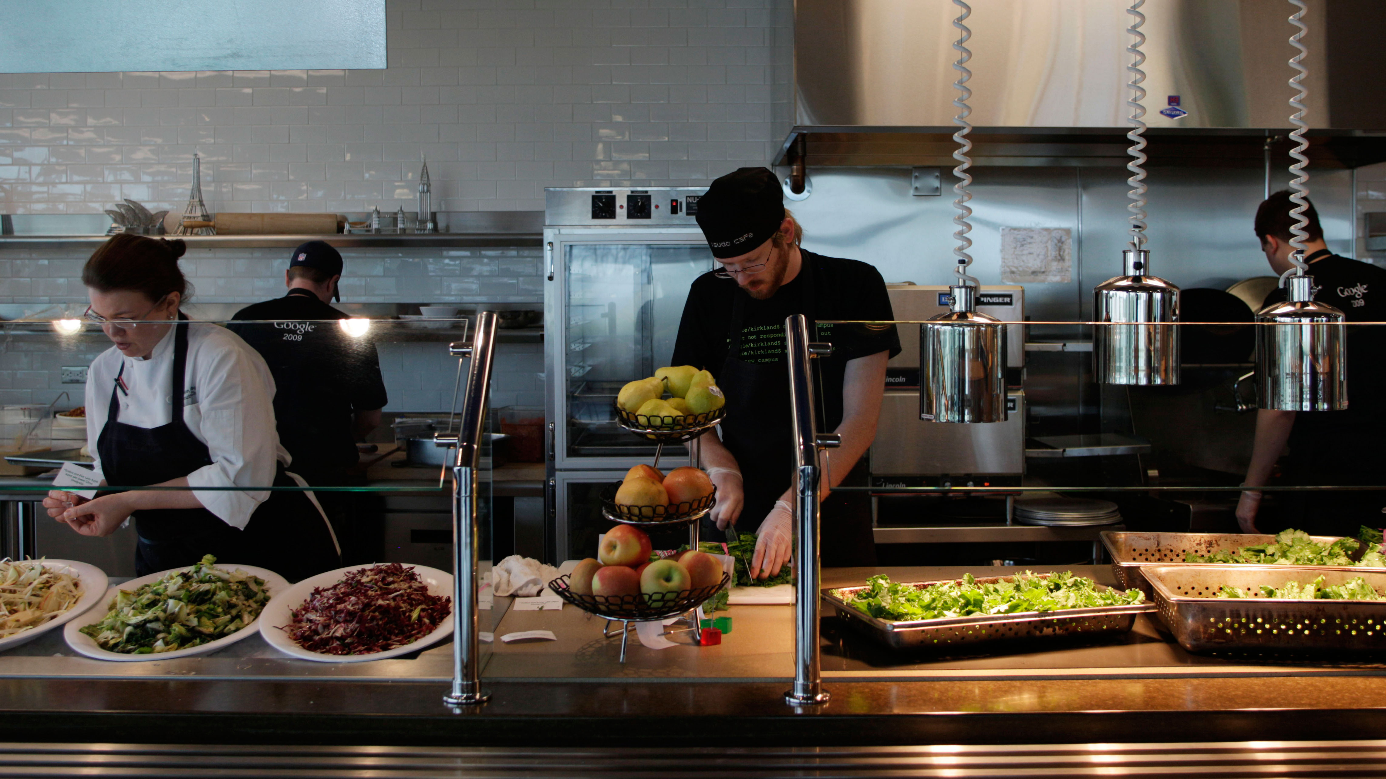 Workers prepare food in the employee cafeteria of Google Inc.'s new campus in Kirkland, Wash., Wednesday, Oct. 28, 2009, during a media open house. More than 350 of Google's approximately 20,000 employees currently work in the Kirkland office and they can eat free at several different kitchen facilities in the building. (AP Photo/Ted S. Warren)