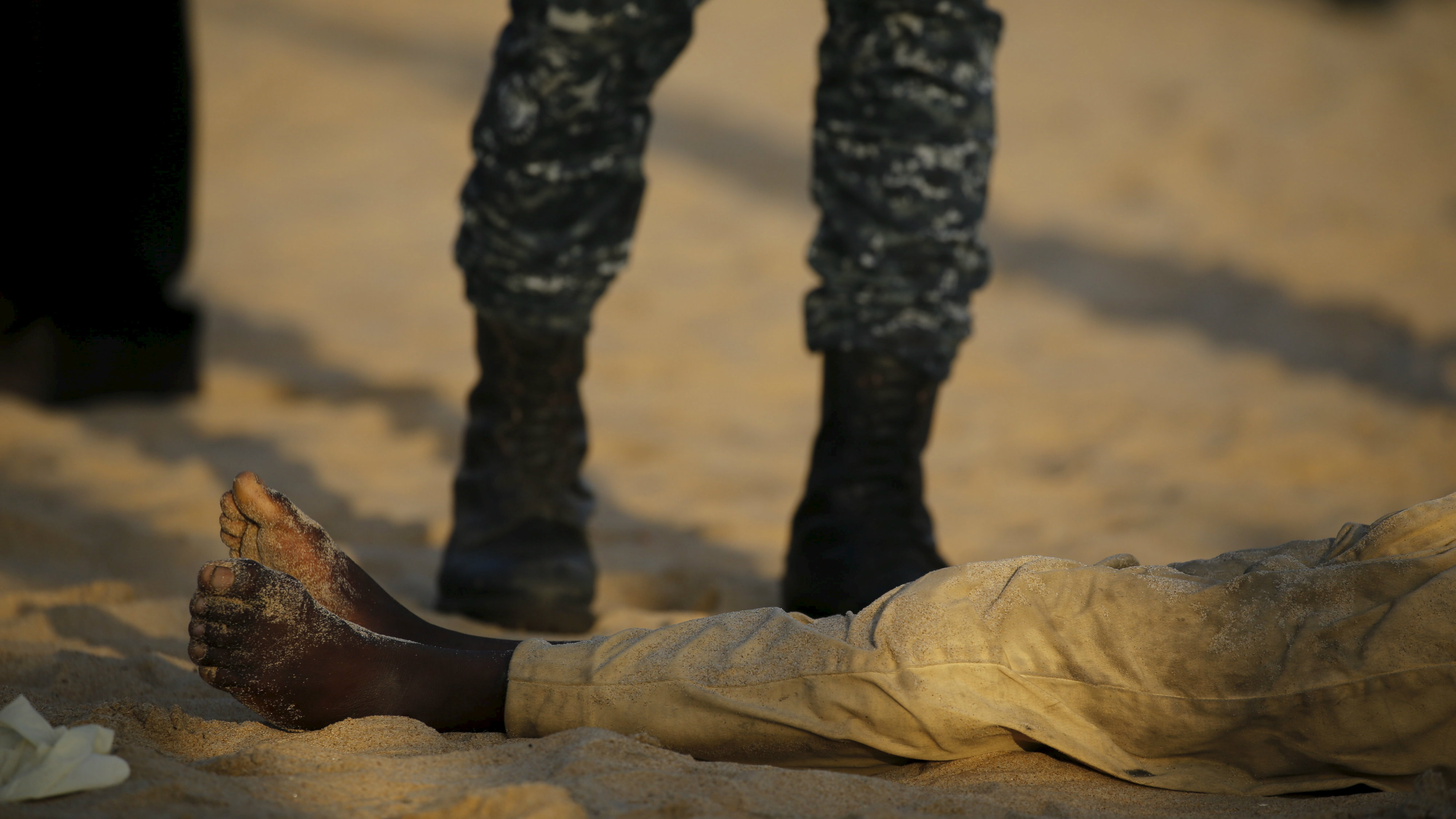 A soldier stands over a person killed on a beach after an attack in Grand Bassam, Ivory Coast, March 13, 2016.