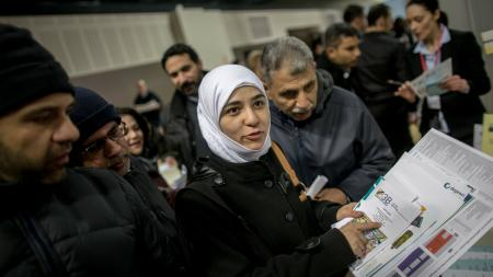 Navin Hassan (26, C) from Damaskus reads anadvert on a job at a hotel at the job fair for refugees in Berlin, Germany, 29 February 2016. Several thousand of refugees came to get information on job and training offers of about 200 companies and educational institutions.