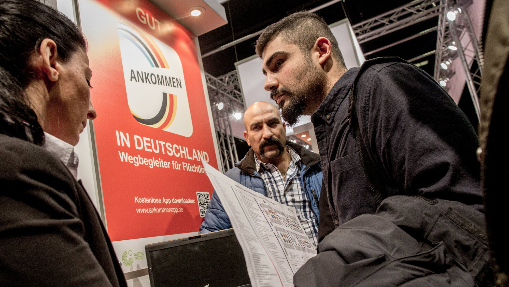 Two men from Iran talk to a staff member at the booth of the German Federal Labour Office at the job fair for refugees in Berlin, Germany, 29 February 2016. Several thousand of refugees came to get information on job and training offers of about 200 companies and educational institutions.