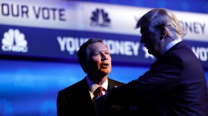 Republican U.S. presidential candidate and Ohio Governor John Kasich (L) talks with businessman Donald Trump (R) as Trump looks at his watch at the conclusion of the 2016 U.S. Republican presidential candidates debate held by CNBC in Boulder, Colorado, October 28, 2015.