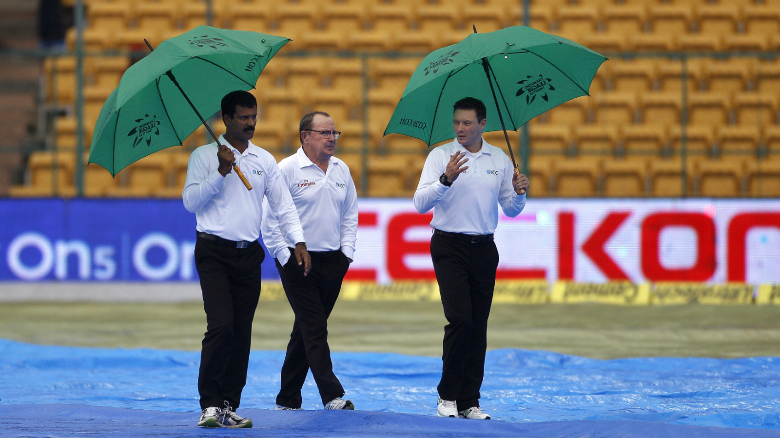 Umpires Ian Gould, center, Richard Allan Kettleborough, right, and C.K. Nandan inspect the outfield before calling off play for the fourth day of second cricket test match between India and South Africa due to rain in Bangalore, India, Tuesday, Nov. 17, 2015. The second test between India and South Africa looked set for a draw Tuesday after no play was possible on the fourth day. (AP Photo/Aijaz Rahi)