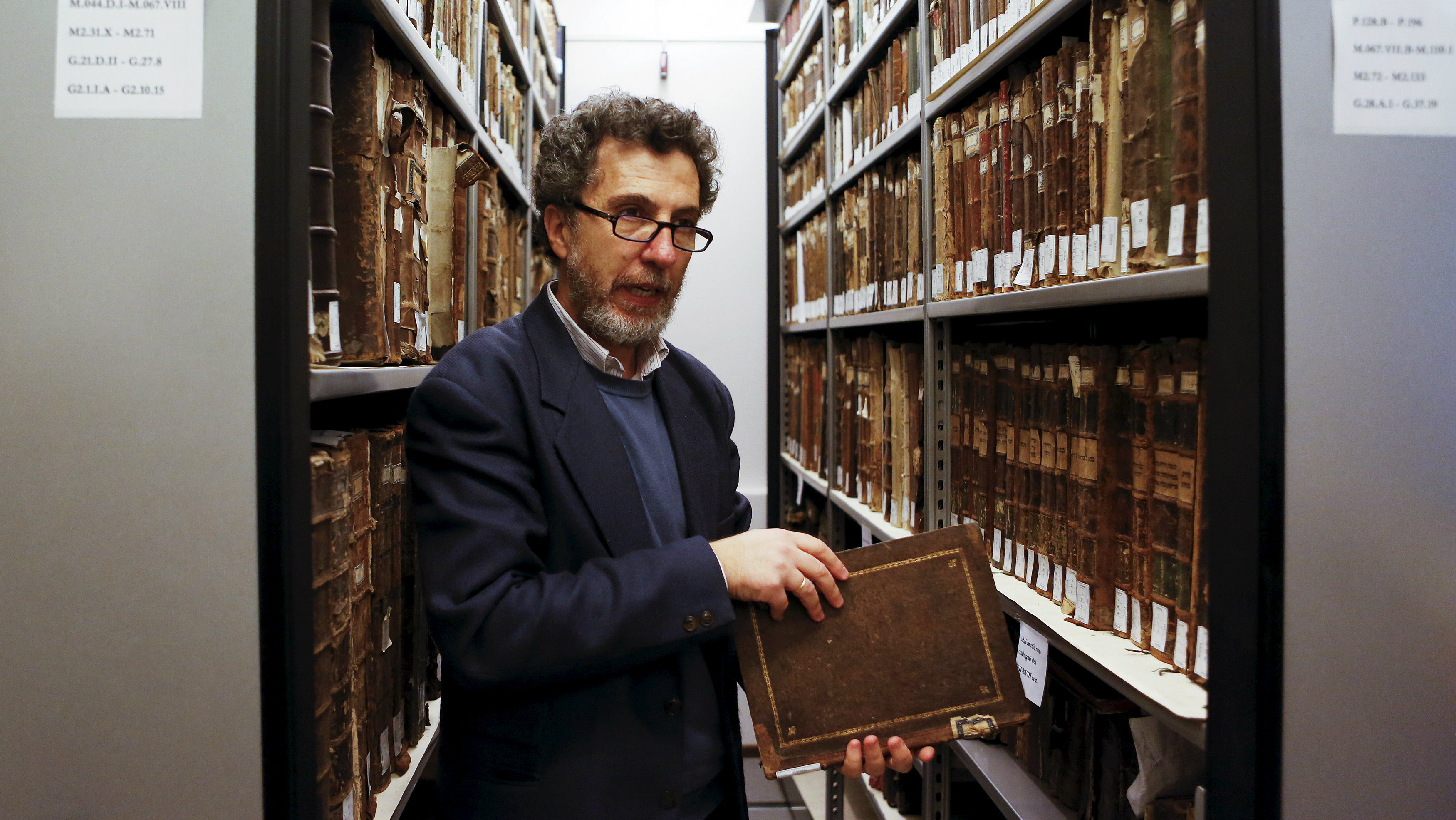 """Professor Gadi Luzzatto Voghera, director of the Jewish Library in the Venice ghetto, looks at manuscripts about Jewish history in the library's vaults, northern Italy, March 22, 2016. The Jews of the world's first ghetto, marking its 500th anniversary, advise patience and integration to Europe as it struggles with the challenge of mass migration. In March 1516 the leader of the Venetian Republic and his senate decreed to confine the city's Jews on an island. Venice gave the world the word """"ghetto"""", with its infamous connotations through the centuries. REUTERS/Alessandro Bianchi SEARCH """"VENICE GHETTO"""" FOR THIS STORY. SEARCH """"THE WIDER IMAGE"""" FOR ALL STORIES"""