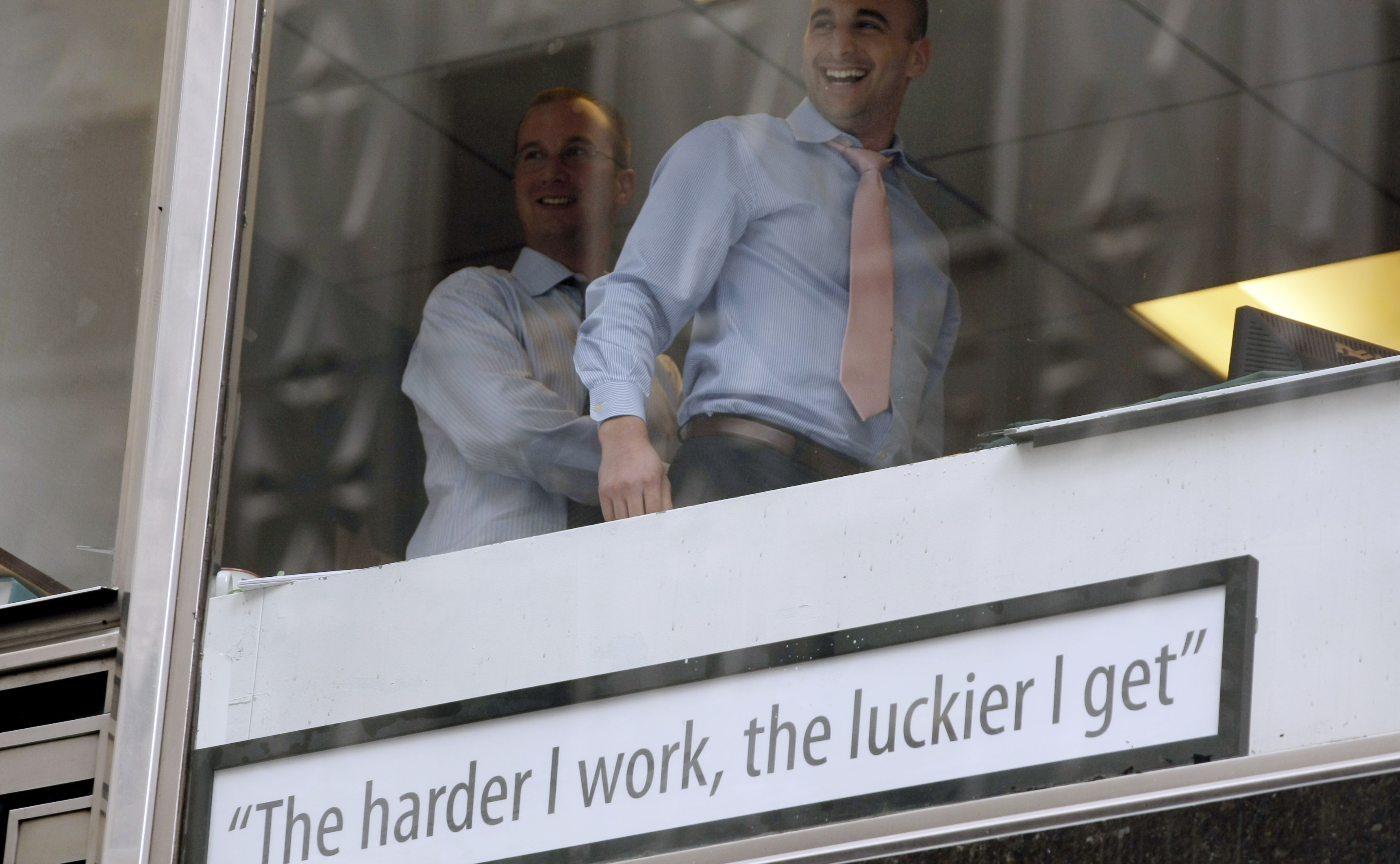 Businessmen in window laugh after placing sign on their window above where Occupy Wall Street protesters were marching along East 42nd street in New York City