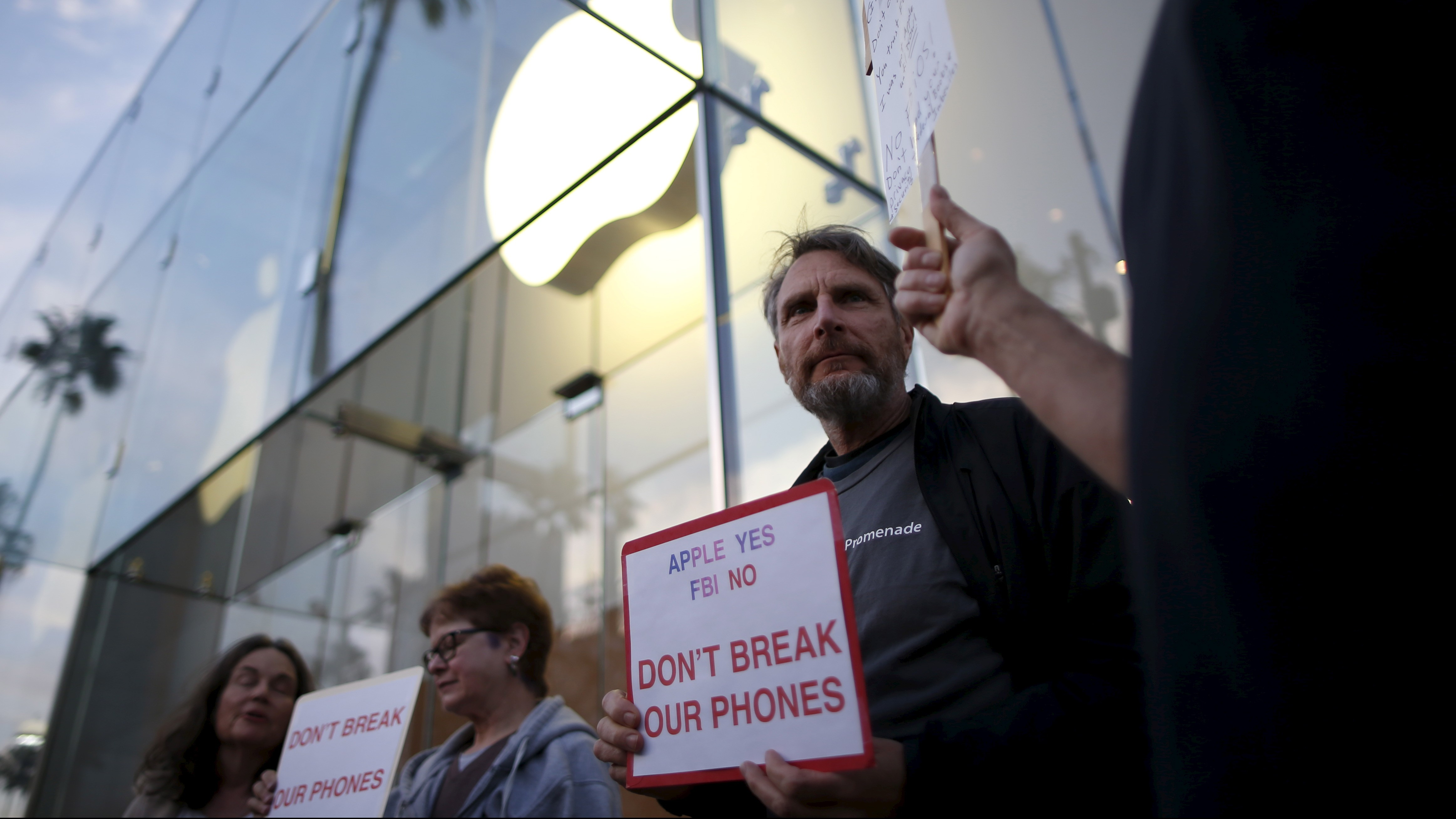 People gather at a small rally in support of Apple's refusal to help the FBI access the cell phone of a gunman involved in the killings of 14 people in San Bernardino, in Santa Monica, California, United States, February 23, 2016.