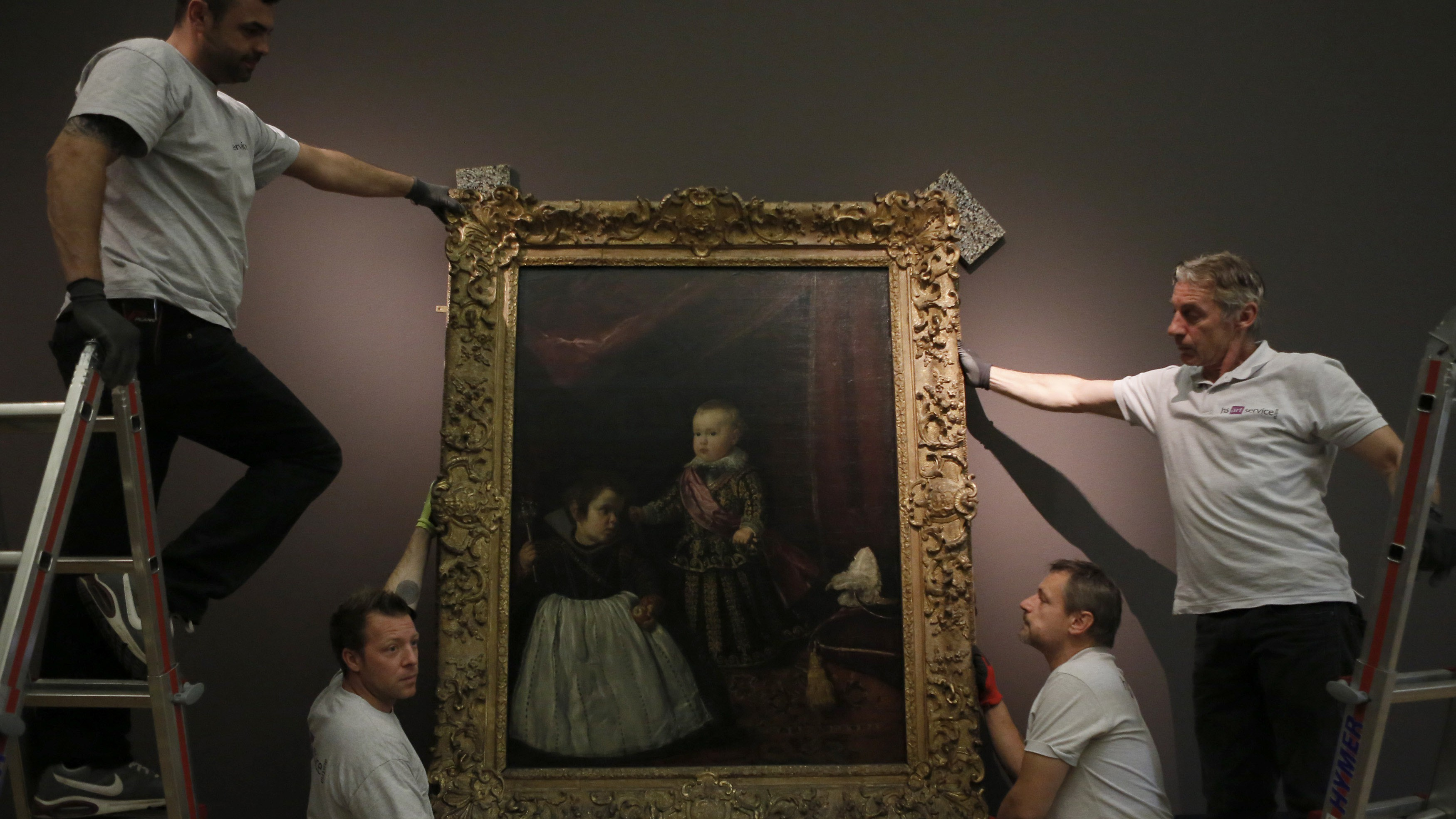 """Employees of Vienna's Art History Museum (Kunsthistorisches Museum Wien) adjust the painting """"Infant Balthasar Charles with a Dwarf"""" by Spanish artist Diego Velazquez, prior to the opening of the major exhibition """"Velazquez"""" in Vienna October 22, 2014. The exhibiton runs from October 28, 2014 to February 15, 2015 in the museum."""