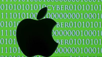 Picture illustration of a 3D printed Apple logo seen in front of a displayed cyber code