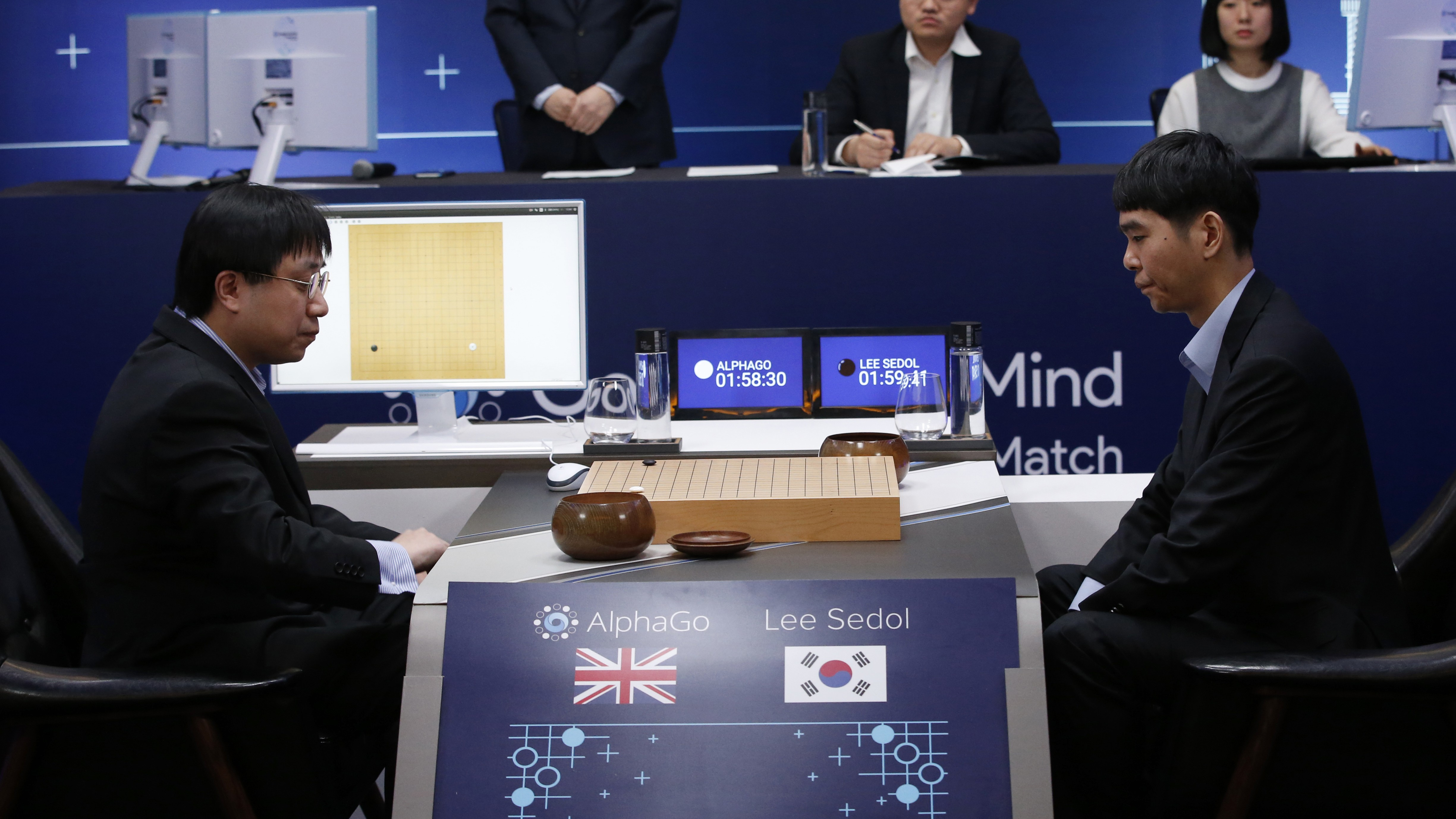 South Korean professional Go player Lee Sedol, right, prepares for his second stone against Google's artificial intelligence program, AlphaGo, as Google DeepMind's lead programmer Aja Huang, left, sits during the Google DeepMind Challenge Match in Seoul, South Korea, Wednesday, March 9, 2016. Google's computer program AlphaGo defeated its human opponent, South Korean Go champion Lee Sedol, on Wednesday in the first game of a historic five-game match between human and computer. (AP Photo/Lee Jin-man)