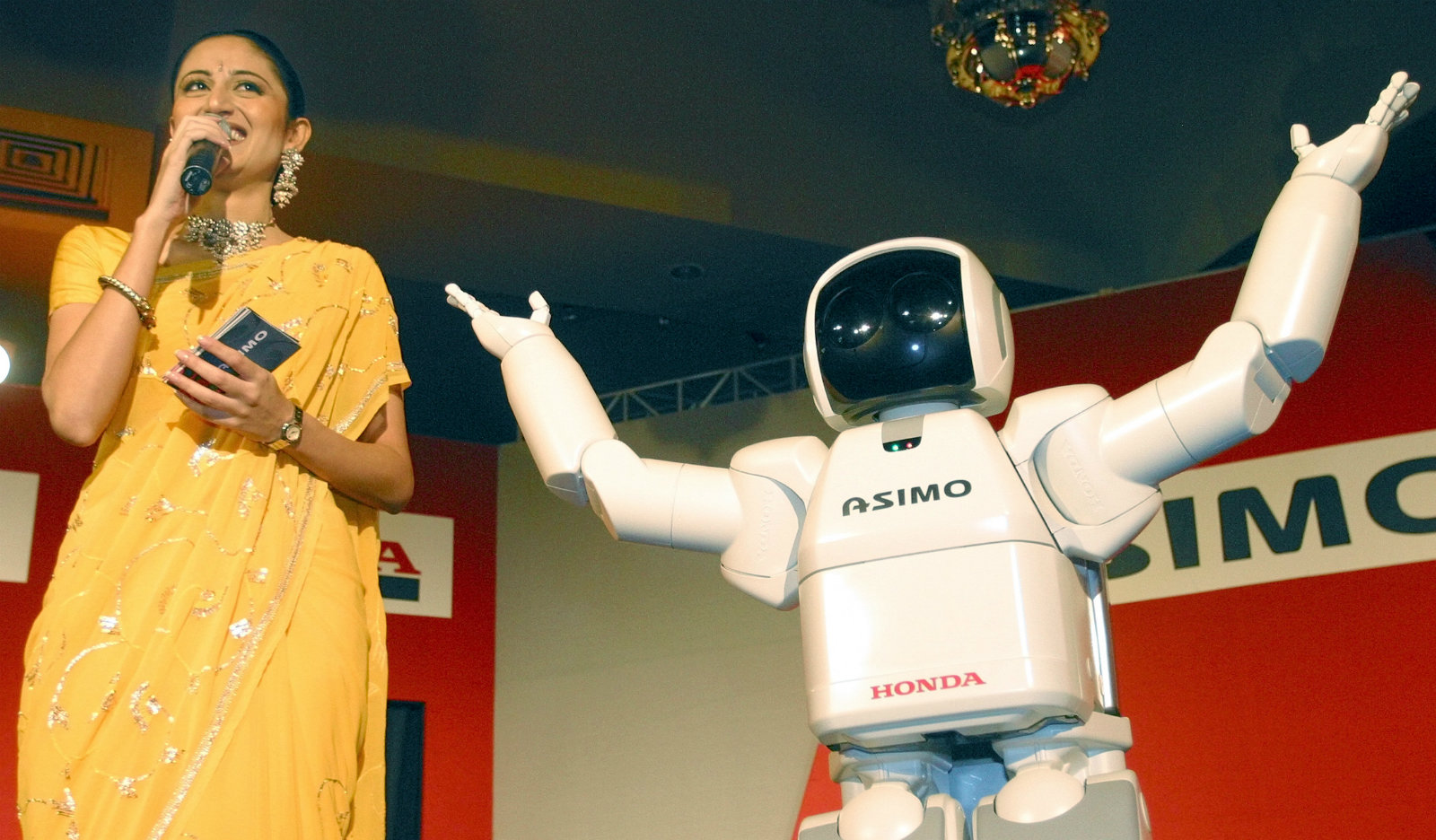 An Indian hostess talks to the media during a media conference at the launch of Honda's ASIMO in New Delhi September 9, 2003. ASIMO, a robot that can walk autonomously, is the world's most advanced humanoid robot.