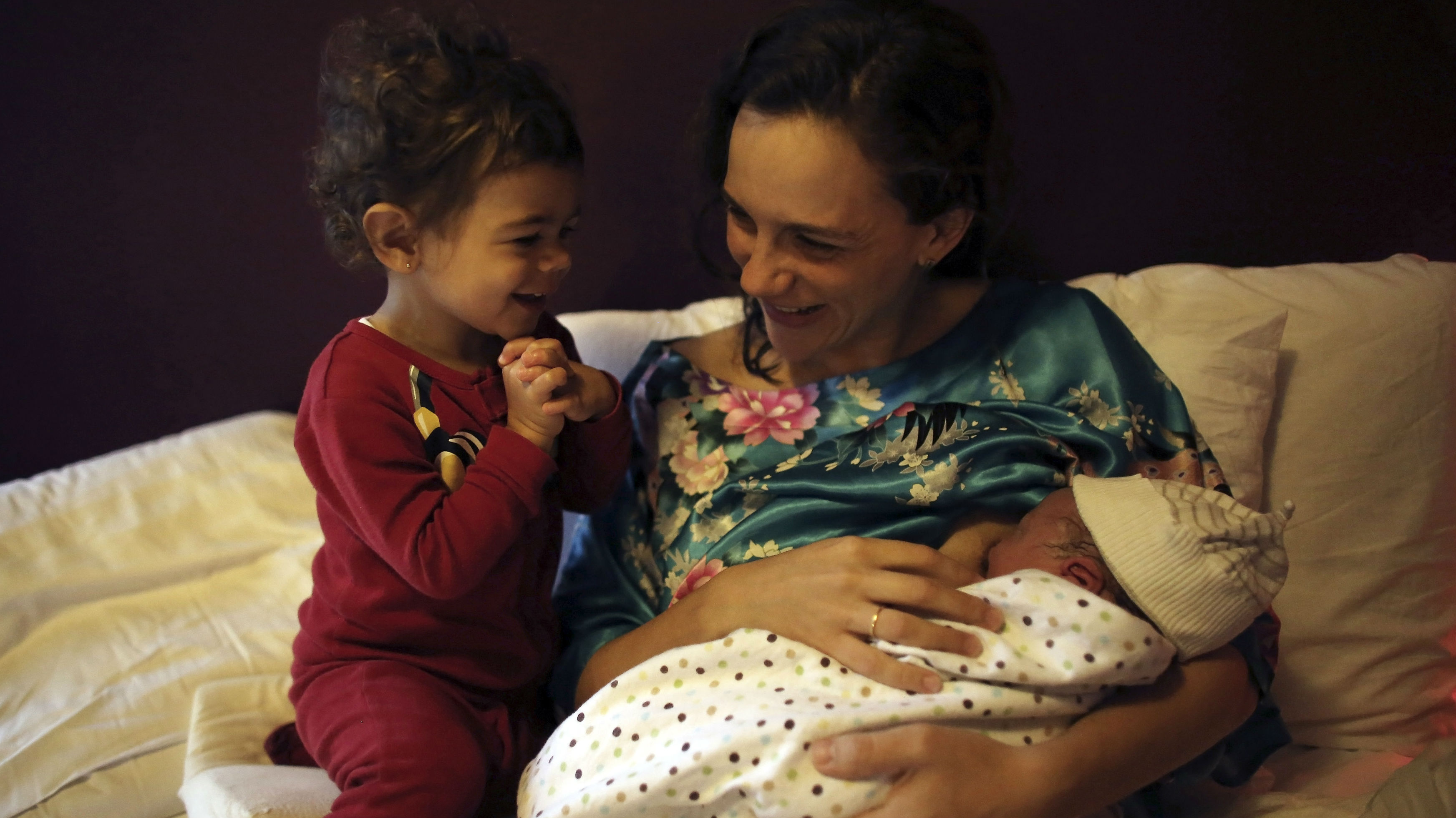 Manuela Mitre nurses her newborn son Gael as her daughter Alice watches at their home in Sao Paulo November 6, 2013. Manuela and her husband Andre decided to have their child born in a pool of warm water, which creates an environment similar to that inside the womb, according to the midwives. Picture taken November 6, 2013.