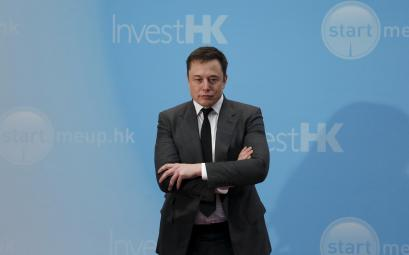 Tesla Chief Executive Elon Musk stands on the podium as he attends a forum on startups in Hong Kong.