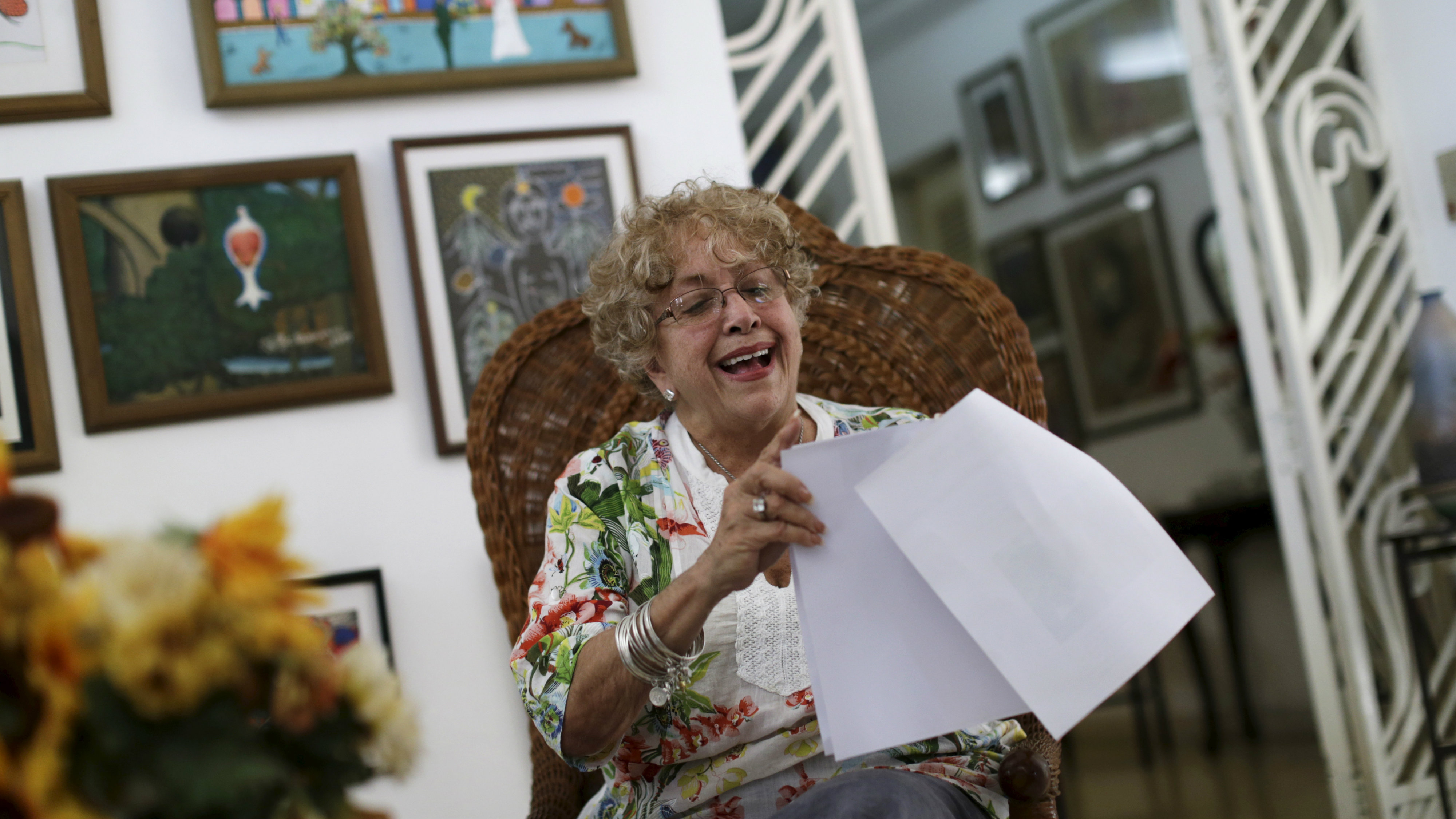 Ileana R. Yarza laughs while holding a print-out of a letter U.S. President Barack Obama is sending her via a flight carrying the first batch of U.S. direct mail to Cuba, after both countries agreed to restore direct postal service after a half-century rupture, at her home in Havana, March 17, 2016. REUTERS/Ueslei Marcelino
