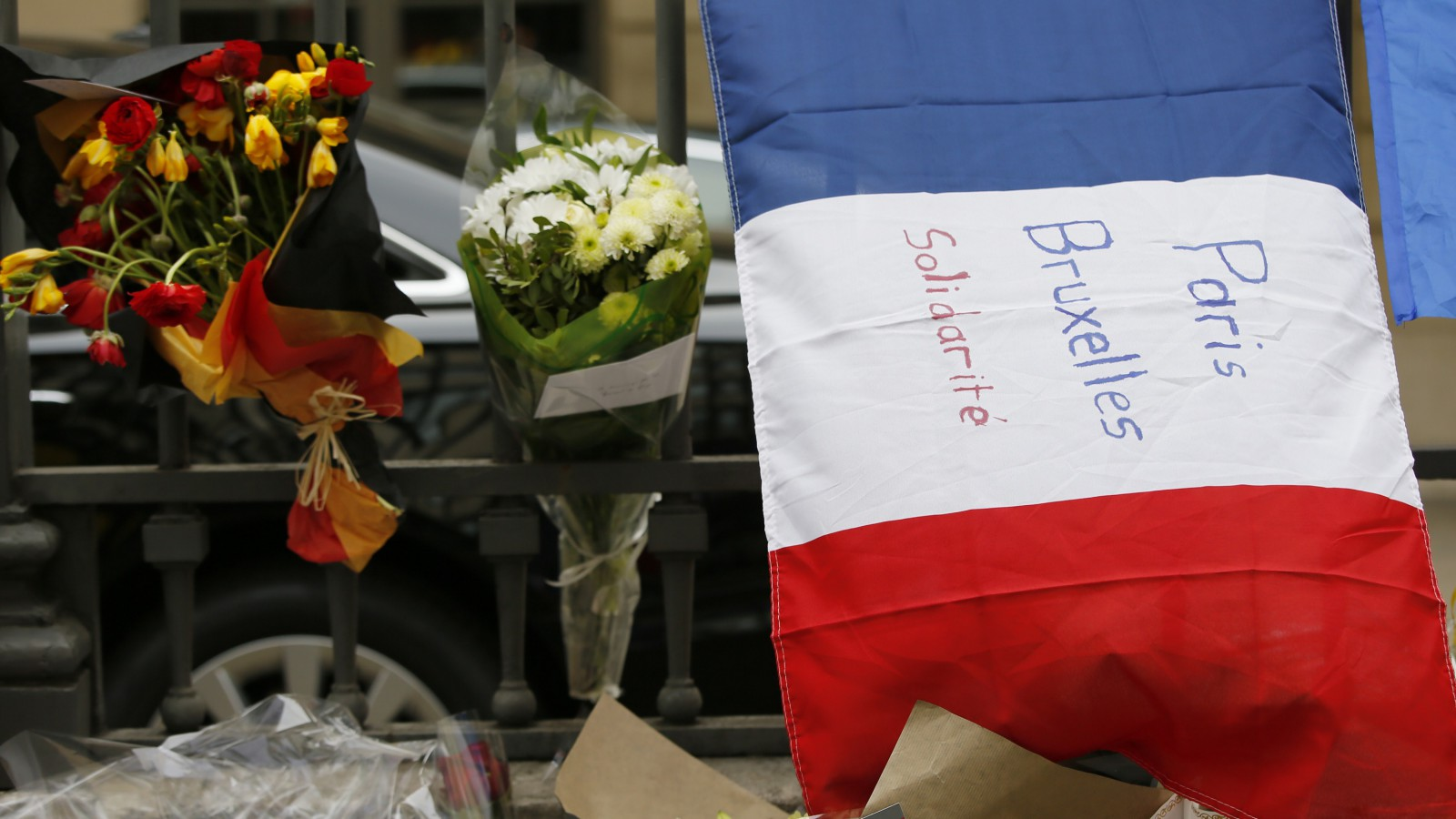 A French flag with the message 'Paris Brussels Solidarity' is displayed next to flowers with the colors of the Belgium flag in front of the Belgium embassy in Paris, France, March 23, 2016 in tribute to the victims of Tuesday's bomb attacks in Brussels.  REUTERS/Gonzalo Fuentes - RTSBUXV