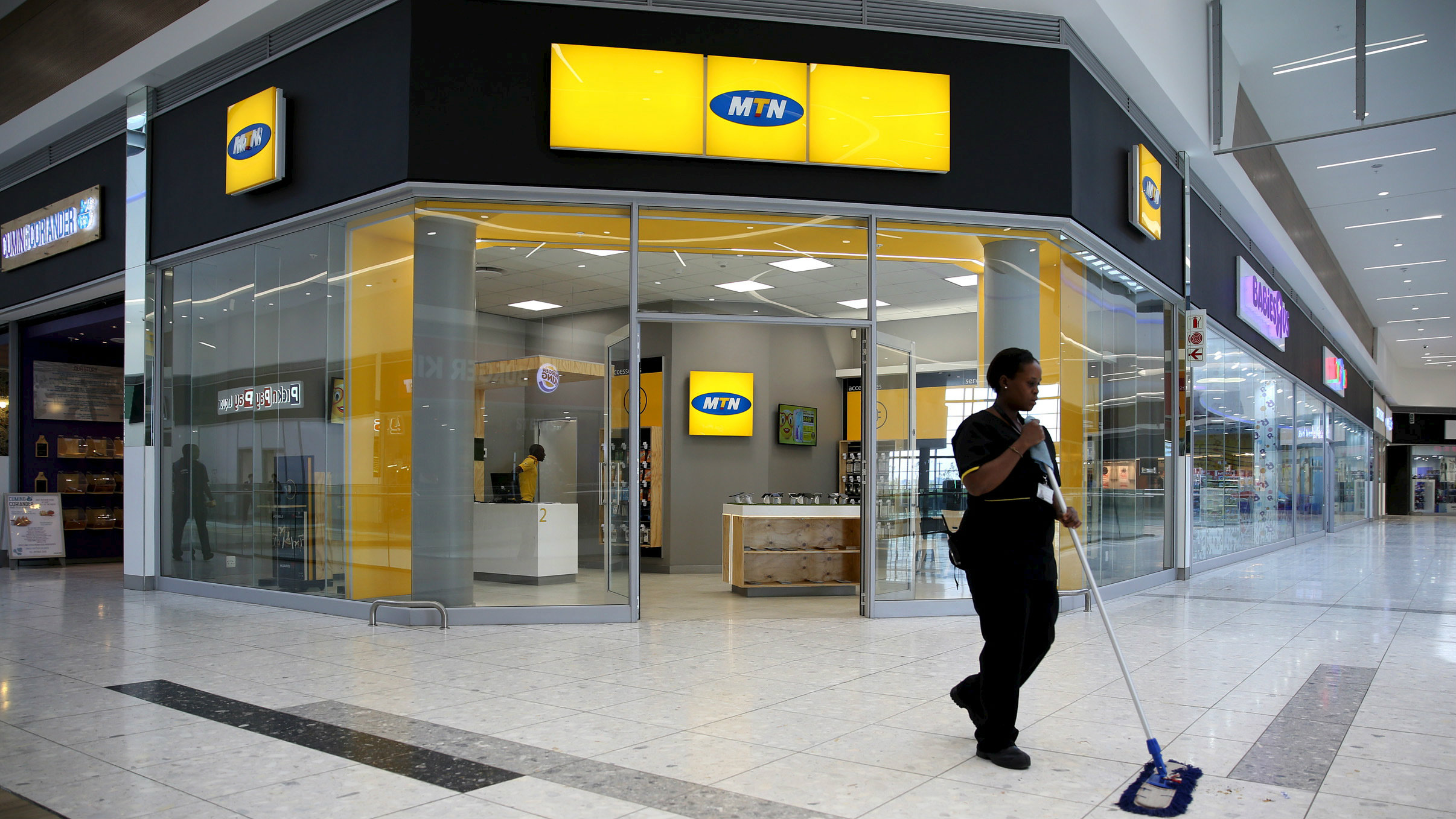 A worker sweeps past an outlet of South Africa's MTN Group in Johannesburg, February 23, 2016.