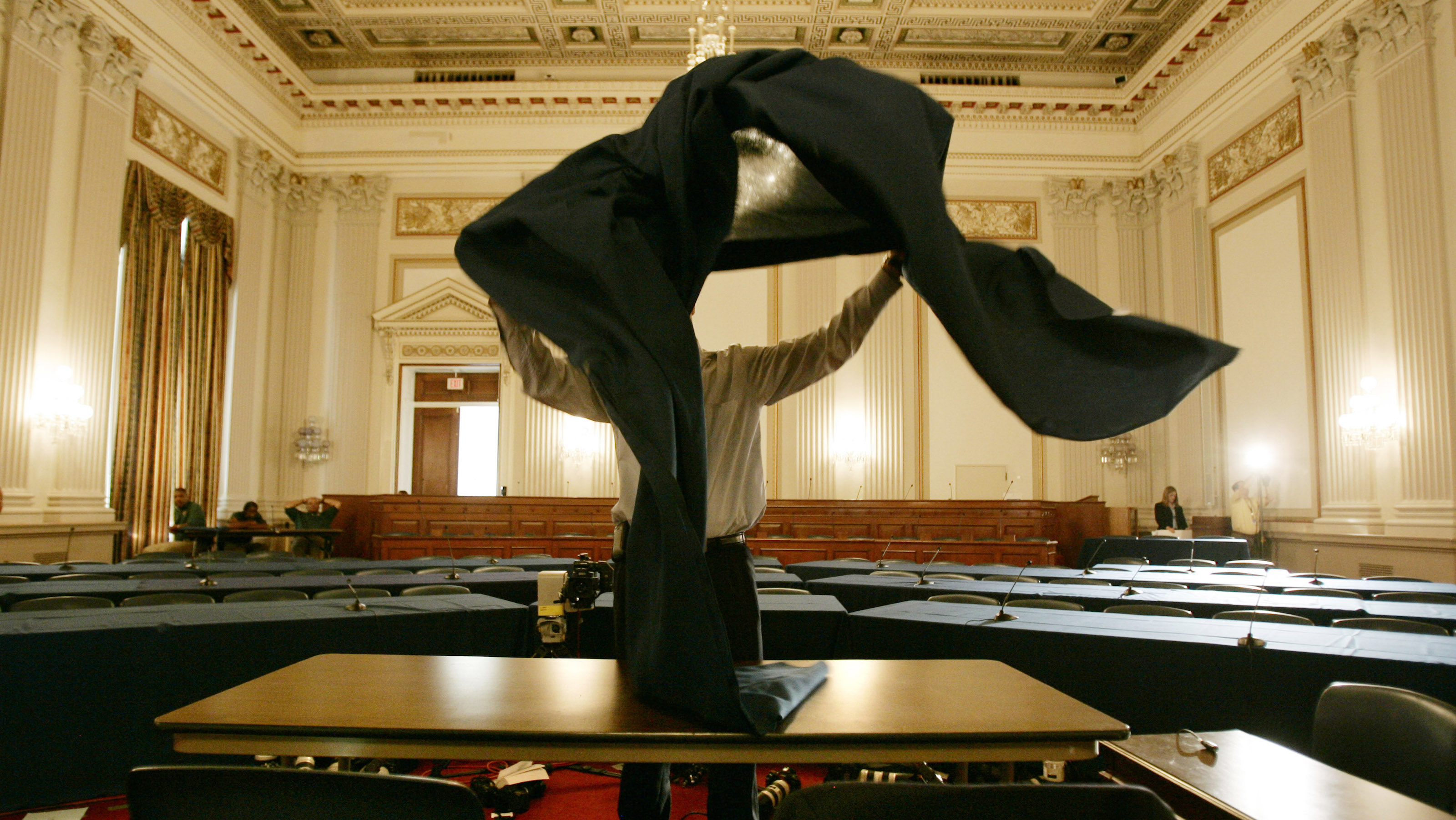 U.S. House Foreign Affairs Committee staffer Riley Moore lays out a tablecloth on a desk in Washington, September 10, 2007, where the U.S. military commander in Iraq, General David Petraeus and U.S. Ambassador to Iraq Ryan Crocker are to expected to report on military progess in Iraq. In the report considered crucial to U.S. strategy in the highly unpopular war in Iraq, Petraeus is expected to tell Congress on Monday that U.S. troop levels should not be cut deeply.        REUTERS/Jason Reed   (UNITED STATES) - RTR1TOKF