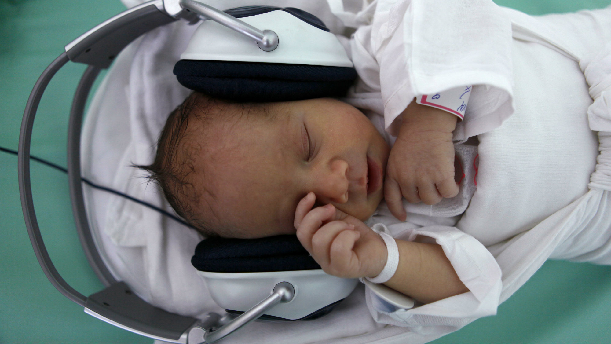 A newborn baby rests in a box, listening to music played through earphones in Saca Hospital in Kosice