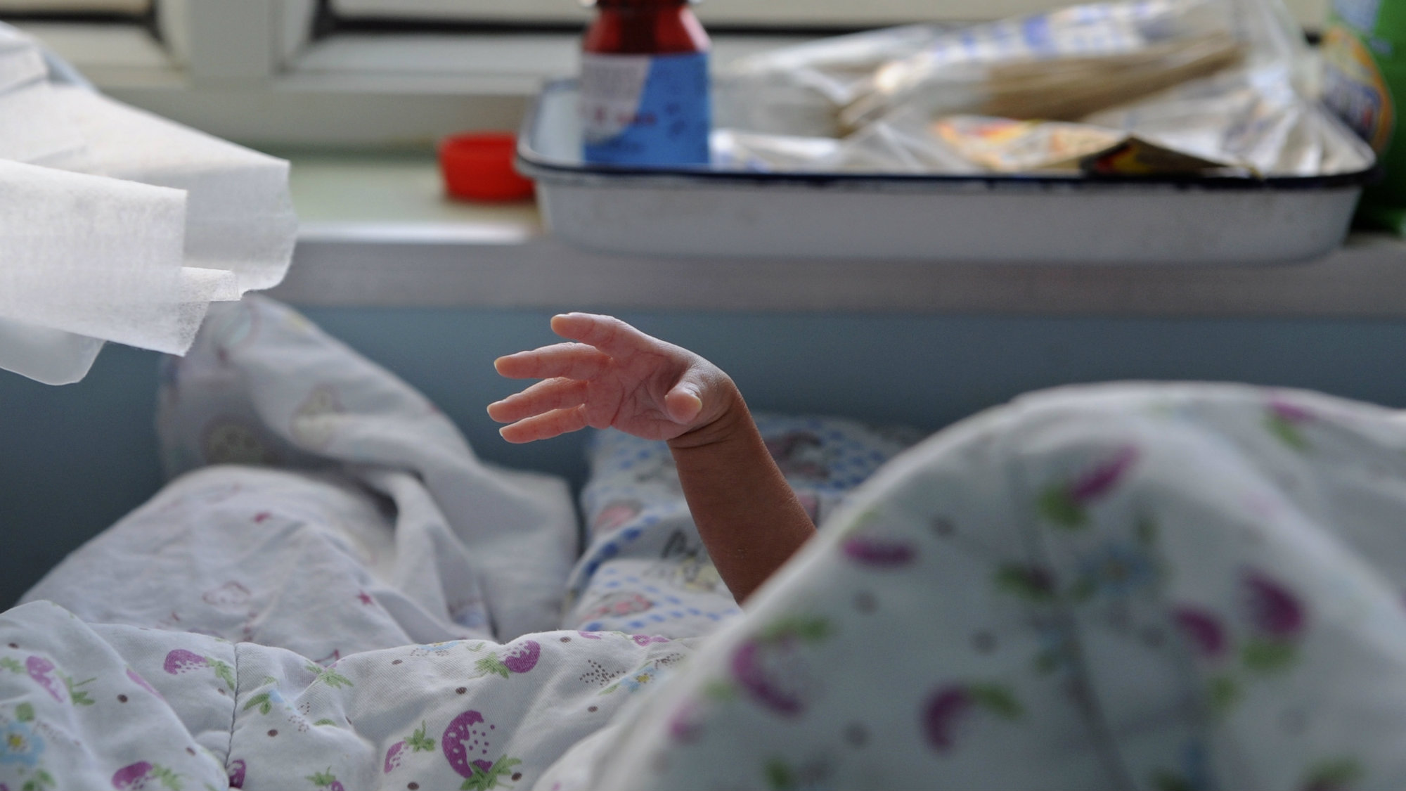 A baby stretches its hand from under a quilt at a local hospital in Jiaxing