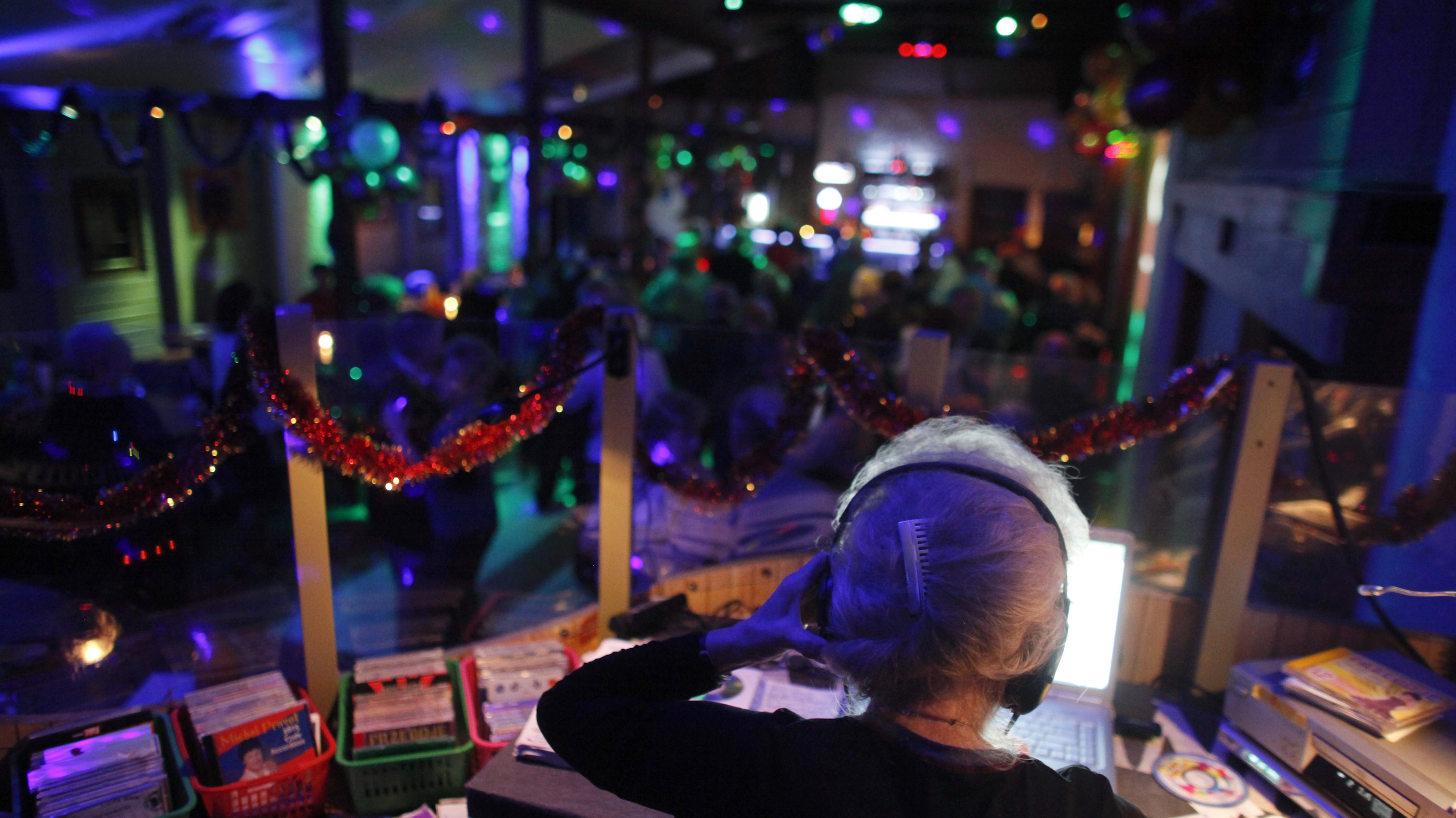 DJ Wika Szmyt plays music at a club in Warsaw January 4, 2012. Szmyt, 73, spends her retirement days behind a DJ console watching people dance to her rhythms. She plays disco, rumba or samba for a mostly elderly audience because she feels she is giving them a new take at life. DJ Wika plays in a Warsaw club three days a week but has also been involved in other musical projects, including parties where she plays for a younger and more demanding audience. REUTERS/Kacper Pempel (POLAND - Tags: SOCIETY ENTERTAINMENT) - RTR2VWA8